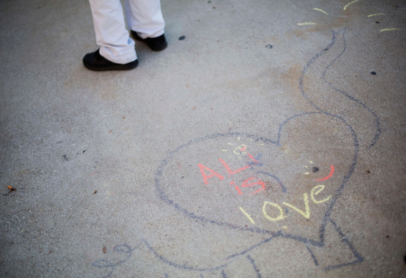 "The message ""Ali is love"" decorates the pavement as members of the public gather outside the box office for tickets for Muhammad Ali's Jenazah service at Freedom Hall Tuesday, June 7, 2016, in Louisville, Ky. The day before his star-studded funeral, members of Ali's Islamic faith will get their chance to say a traditional goodbye during a Jenazah, a traditional Muslim funeral. (AP Photo/David Goldman)"
