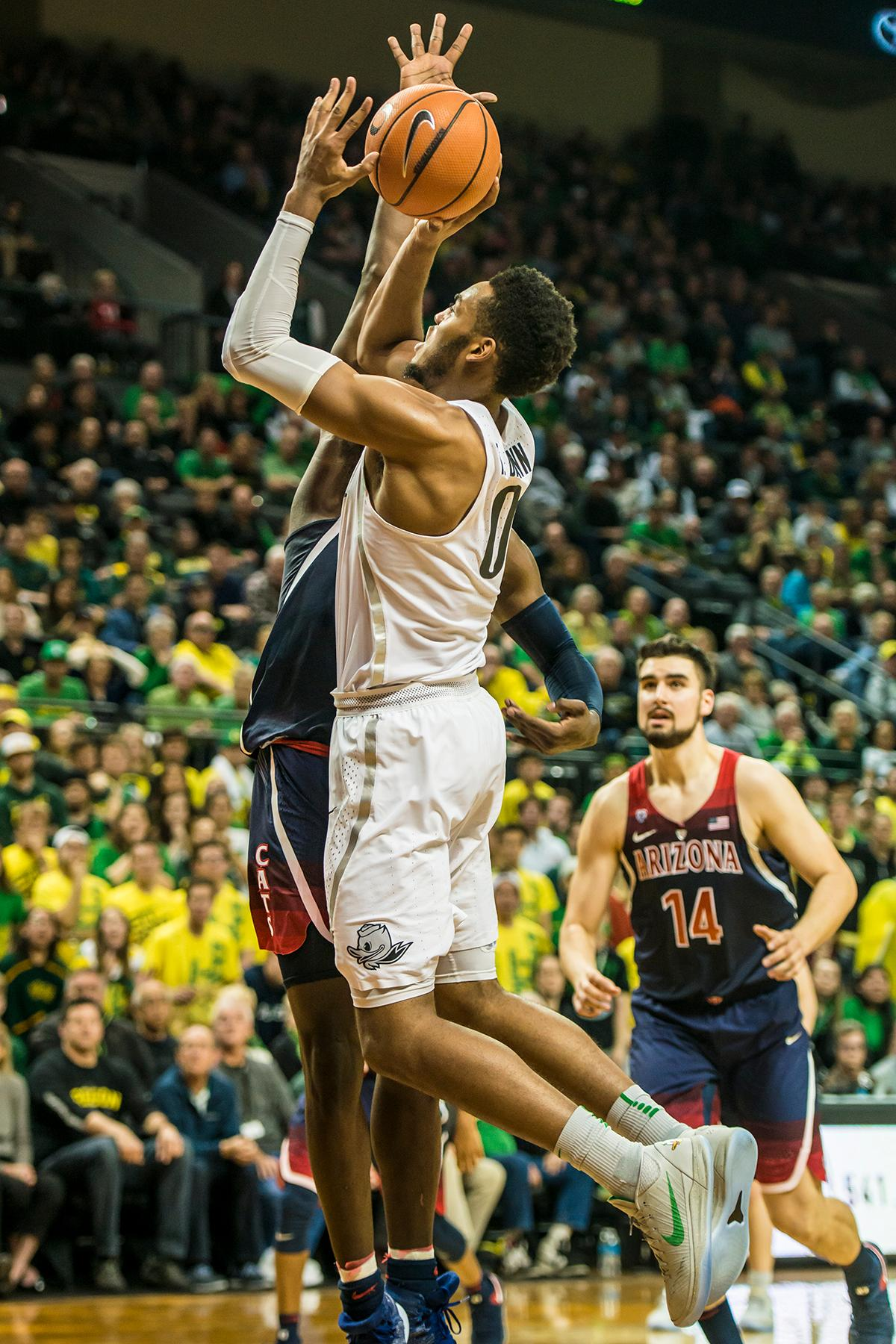 Oregon's Troy Brown jr. shoots against an Arizona defender in theor matchup at Matthew Knight Arena Saturday. The Ducks upset the fourteenth ranked Wildcats 98-93 in a stunning overtime win in front of a packed house of over 12,000 fans for their final home game to improve to a 19-10 (9-7 PAC-12) record on the season. Oregon will finish out regular season play on the road in Washington next week against Washington State on Thursday, then Washington on the following Saturday. (Photo by Colin Houck)