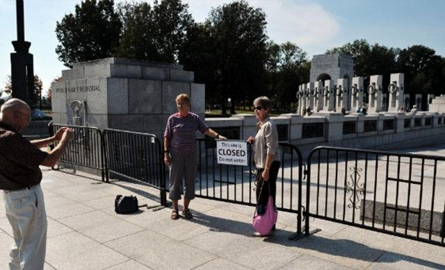 Tourists take photos in front of a barricade blocking access to the World World II Memorial in Washington on Sunday, October 6. The federal government entered a shutdown on October 1. More than 800,000 workers have been furloughed.