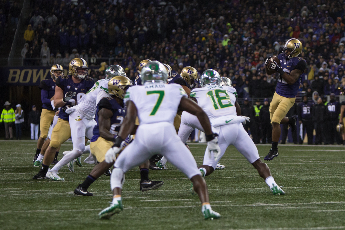 Washington receiver Salvon Ahmed (#26) jumps up to catch a short pass from quarterback Jake Browning (#3). The Oregon Ducks are trailing the Washington Huskies 3 - 17 at halftime.  The Huskies rallied with a 17-point second quarter after a slow first quarter on a cold and rainy night in Seattle, Washington.  Photo by Austin Hicks, Oregon News Lab
