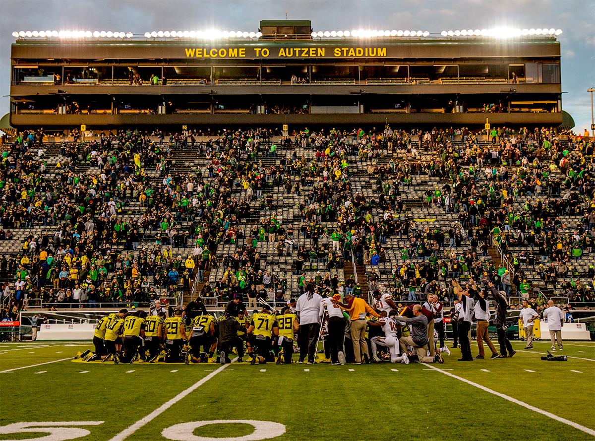 The Duck's team are framed against the Autzen stands after breaking their losing streak by defeating the ASU Sun Devils on Saturday 54-35. Photo by August Frank, Oregon News Lab