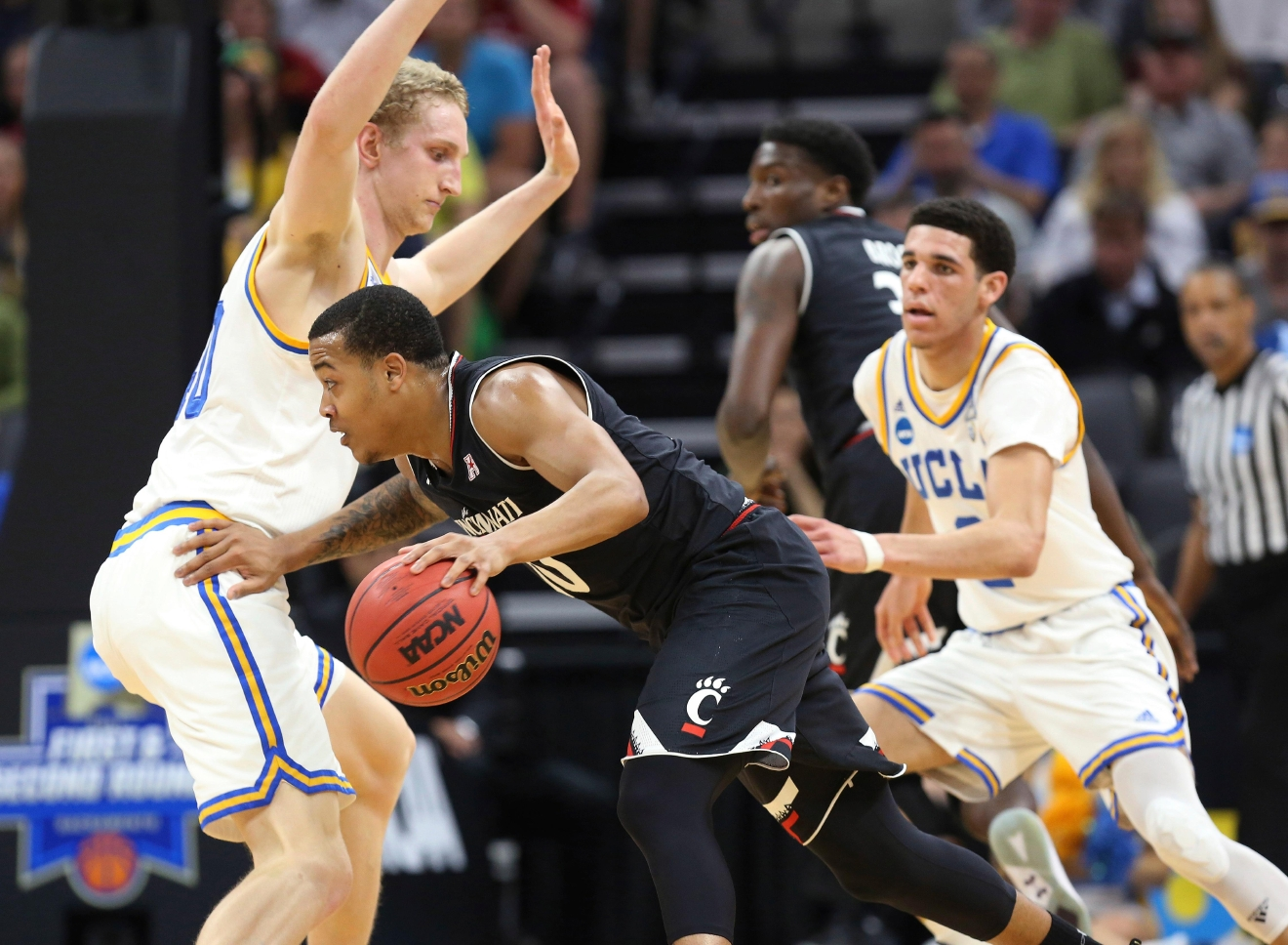 Cincinnati guard Troy Caupain, right, drives against UCLA center Thomas Welsh, left, during the first half of a second-round game of the NCAA men's college basketball tournament in Sacramento, Calif., Sunday, March 19, 2017. (AP Photo/Steve Yeater)