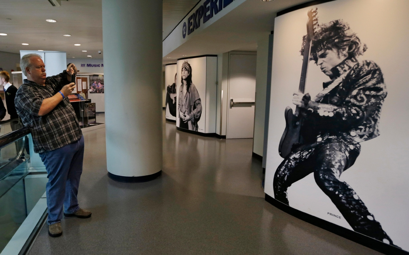 Miles Smith, from Houston, Texas, takes a picture of a mural of Prince at the Rock and Roll Hall of Fame and Museum, Friday, April 22, 2016, in Cleveland. The pop star died Thursday at the age of 57. (AP Photo/Tony Dejak)