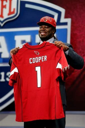 Jonathan Cooper from North Carolina holds up the team jersey after being selected seventh overall by the Arizona Cardinals in the first round of the NFL football draft, Thursday night.