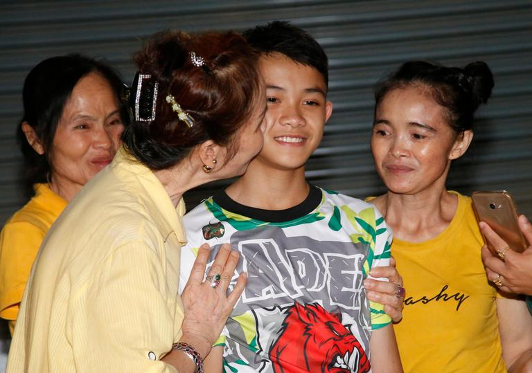 Relatives of Duangpetch Promthep, one of the boys rescued from the flooded cave in northern Thailand, greet him as he arrives home in the Mae Sai district, Chiang Rai province, northern Thailand, Wednesday, July 18, 2018. The 12 boys and their soccer coach rescued from a cave in northern Thailand left the hospital where they had been recuperating and appeared at a news conference Wednesday, saying the ordeal made them stronger and taught them not to live carelessly. (AP Photo/Sakchai Lalit)