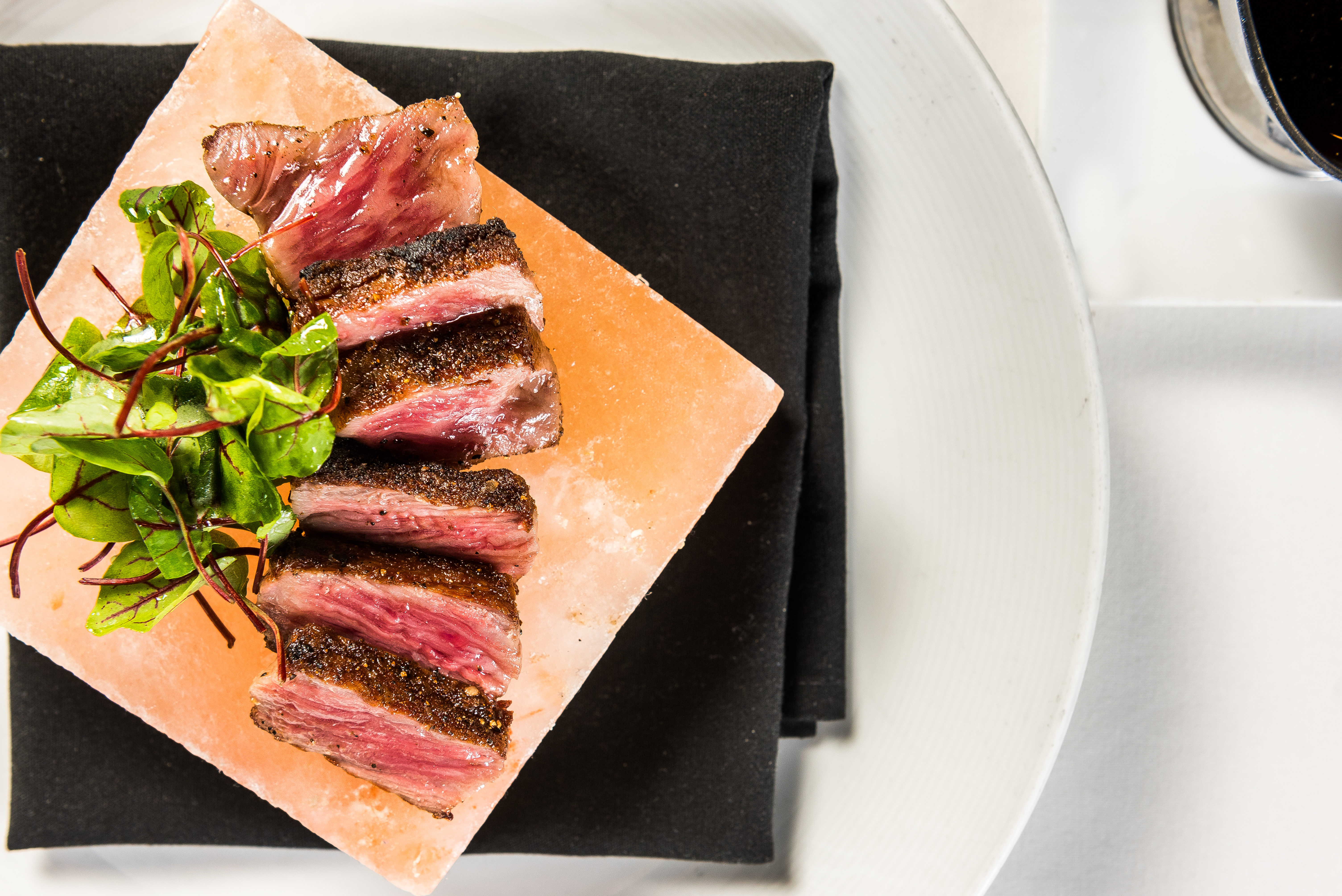 Chef Mike Ellis speedily sears a three-ounce portion on the plancha and serves it on a Himalayan salt block along with a citrus-y red veined sorrel salad and a soy-dashi dipping sauce that has a understated wasabi wallop. (Image: Courtesy Charlie Palmer Steak)