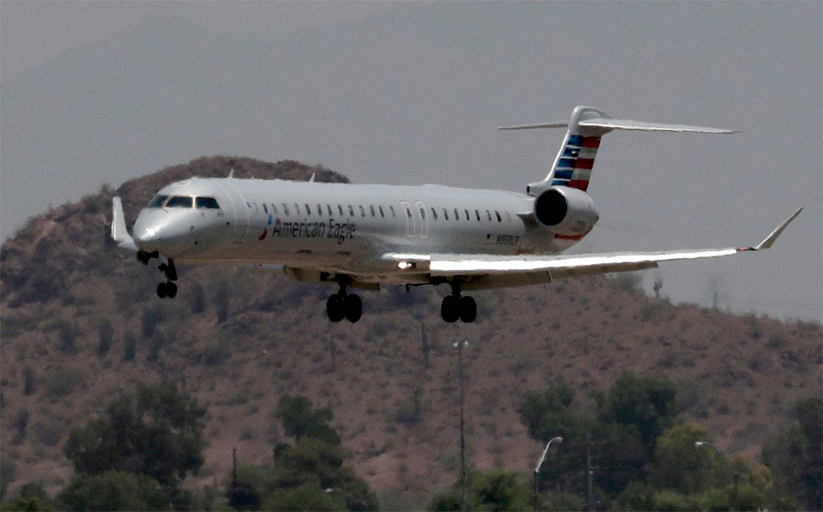 An American Eagle jet is seen through heat ripples as it lands at Sky Harbor International Airport, Monday, June 19, 2017 ,in Phoenix. American Airlines cancelled dozens flights out of Phoenix today due to extreme heat. The cancellations are for operations by smaller regional jets that have lower maximum operating temperatures than full size jets. The smaller jets can't operate when it's 118 degrees or higher. (AP Photo/Matt York)