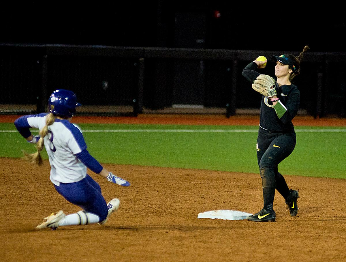 Ducks second base player Lauren Lindvall (#8) attempts to turn a double play. In Game Two of a three-game series, the University of Oregon Ducks softball team defeated the University of Washington Huskies 4-1 Friday night in Jane Sanders Stadium. Danica Mercado (#2), Alexis Mack (#10) and Mia Camuso (#7) all scored in the win, Mack twice. The Ducks play the Huskies for the tie breaker on Saturday with the first pitch at noon. Photo by Dan Morrison, Oregon News Lab