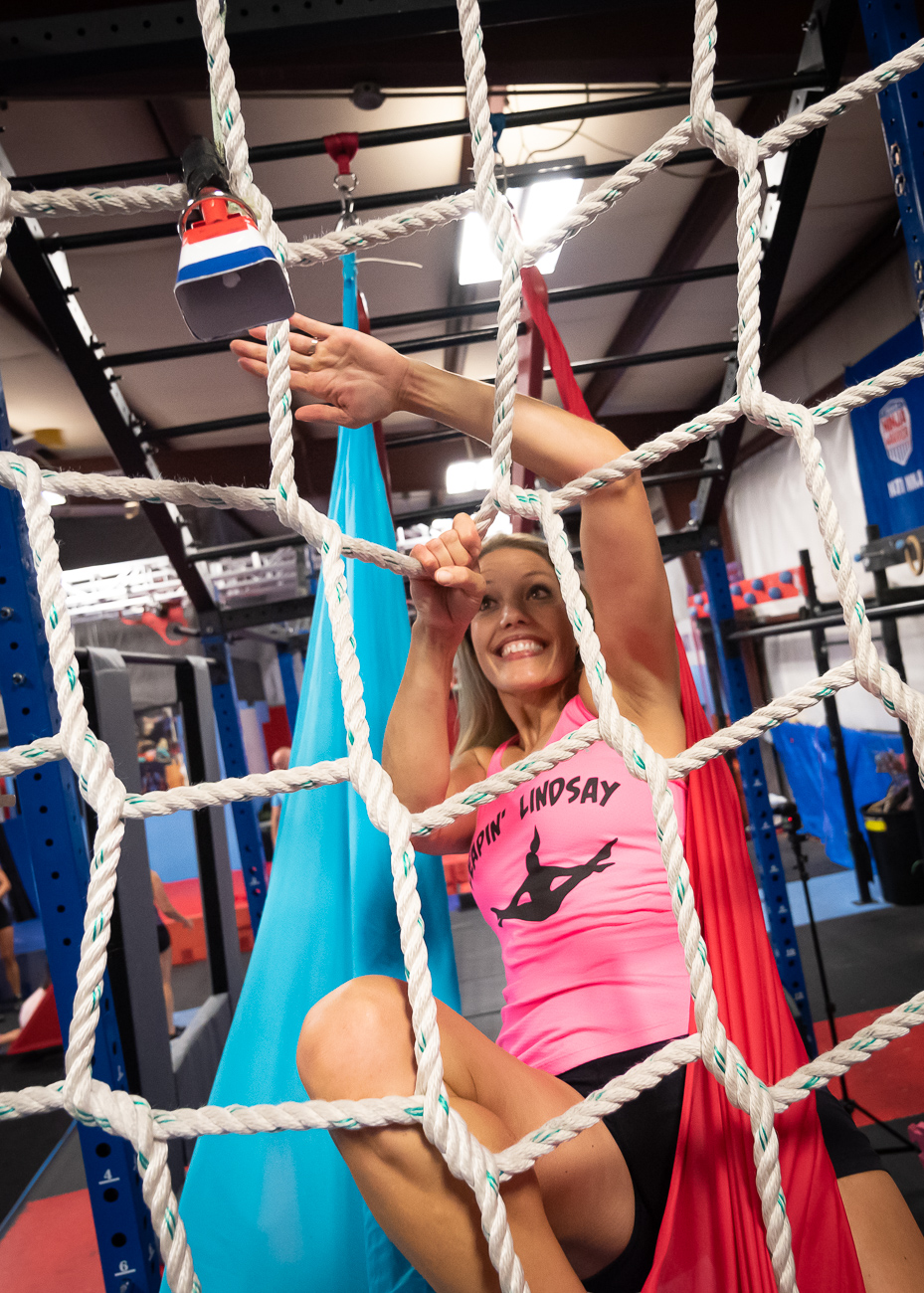 Lindsay Partenio successfully makes it to the climbing net and slaps the victory bell. She appeared on season 11 of American Ninja Warrior. / Image: Phil Armstrong, Cincinnati Refined // Published: 9.18.19