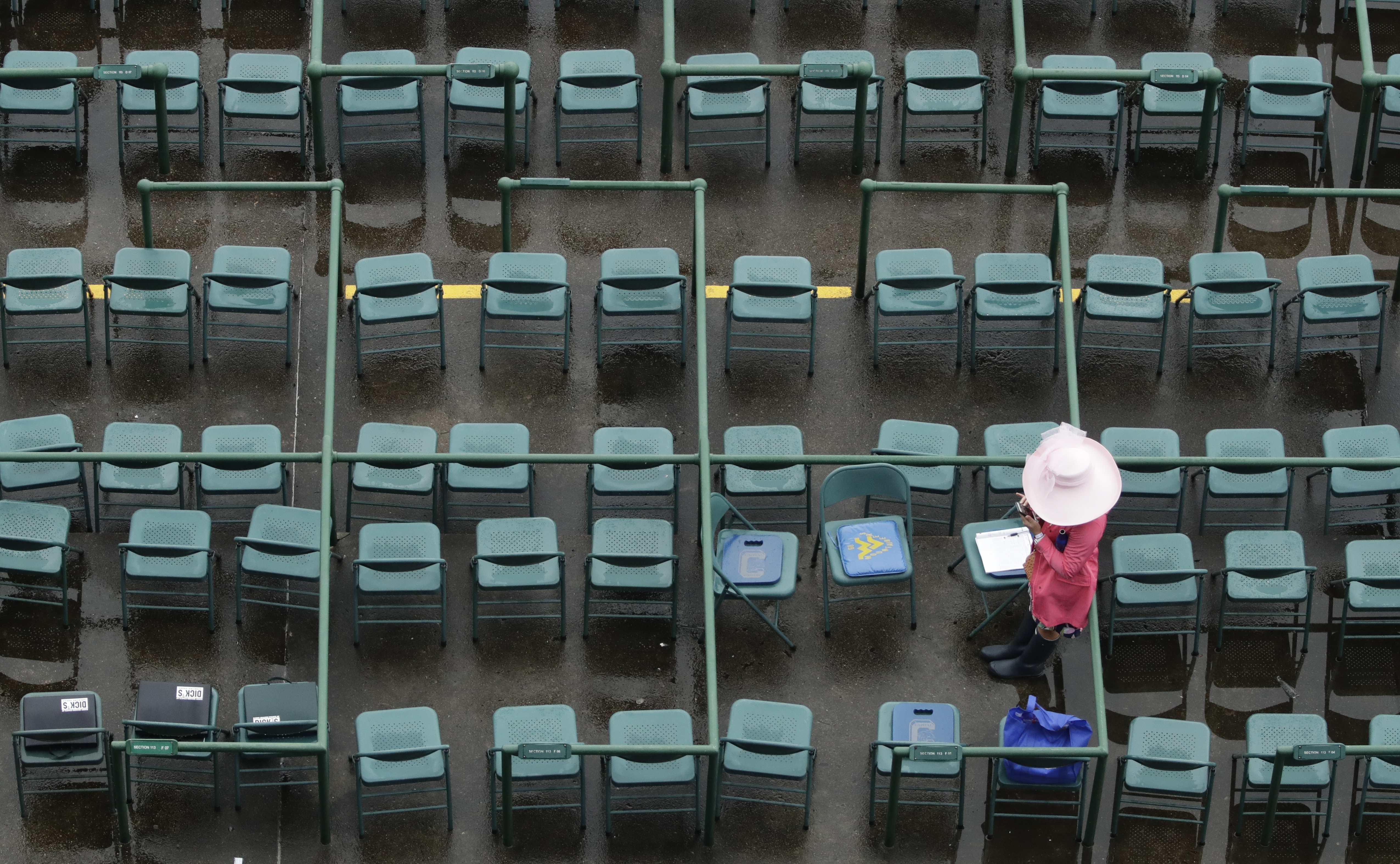 A woman looks at her phone before the 143rd running of the Kentucky Derby horse race at Churchill Downs Saturday, May 6, 2017, in Louisville, Ky. (AP Photo/Charlie Riedel)