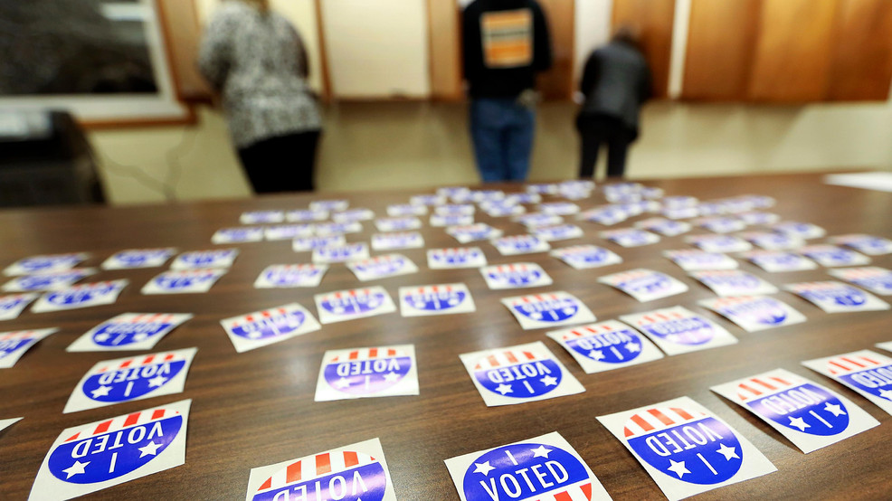 FILE - In this Nov. 6, 2018 file photo, people vote at Jamestown Town Hall in Kieler, Wis. Conservatives are asking a judge to find the Wisconsin Elections Commission in contempt for not immediately purging more than 200,000 voters from the rolls. A judge last month ordered the purge of voters who may have moved and didn't respond within 30 days to notification sent by the elections commission in October 2019.