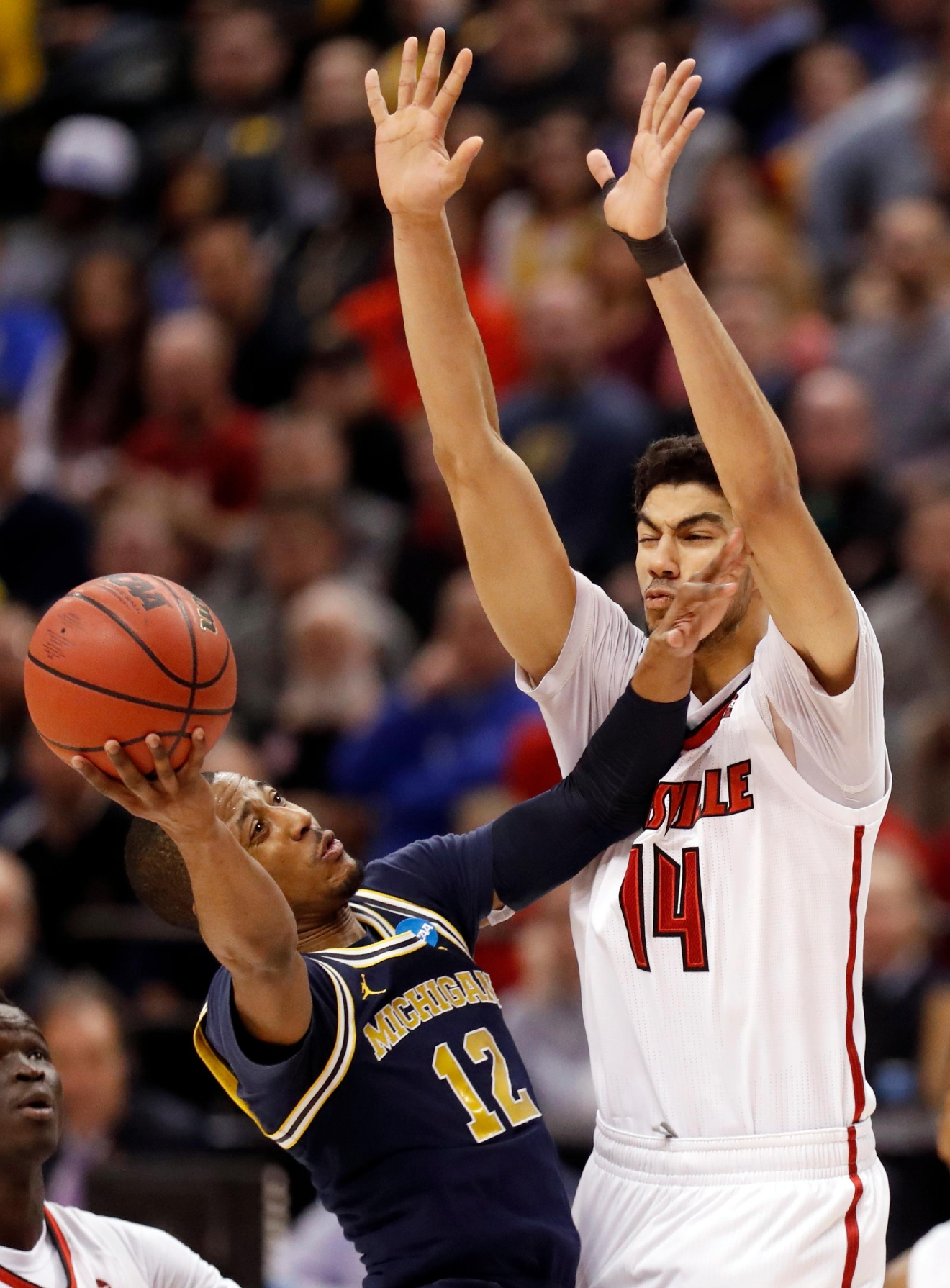 Michigan's Muhammad-Ali Abdur-Rahkman (12) heads to the basket as Louisville's Anas Mahmoud (14) defends during the second half of a second-round game in the men's NCAA college basketball tournament Sunday, March 19, 2017, in Indianapolis. Michigan won 73-69. (AP Photo/Jeff Roberson)