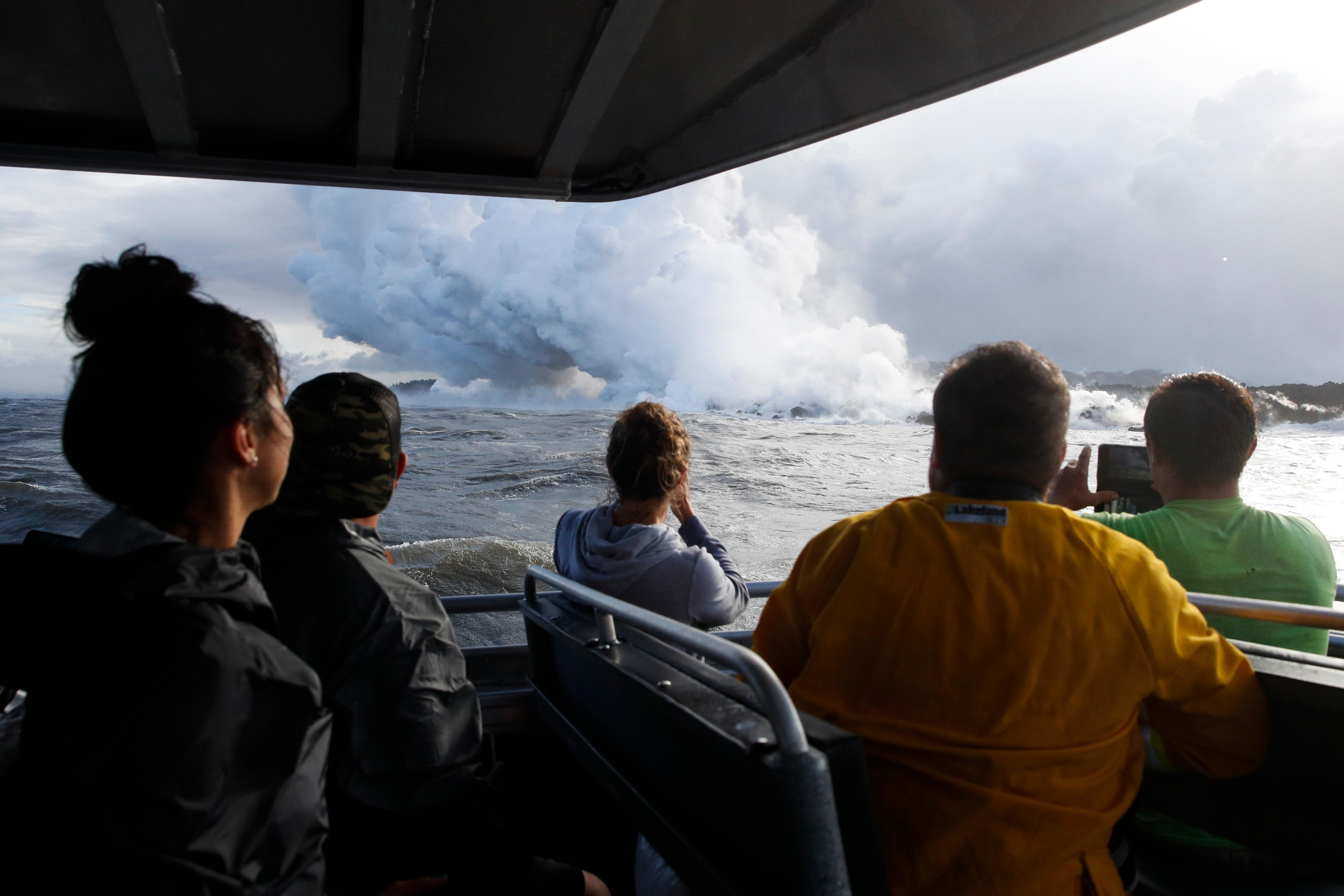 People watch a plume of steam as lava enters the ocean near Pahoa, Hawaii, Sunday, May 20, 2018. Kilauea volcano that is oozing, spewing and exploding on Hawaii's Big Island has gotten more hazardous in recent days, with rivers of molten rock pouring into the ocean Sunday and flying lava causing the first major injury. (AP Photo/Jae C. Hong)