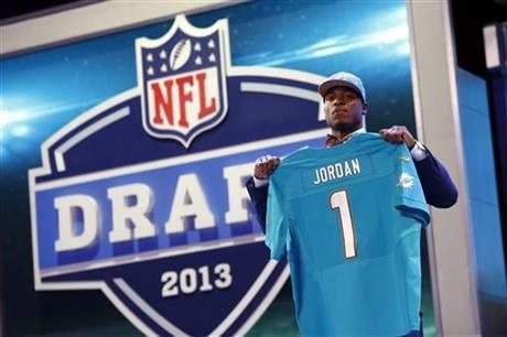 Defensive End Dion Jordan from Oregon stands with the team jersey after being selected third overall by the Miami Dolphins in the first round of the NFL football draft, Thursday night.