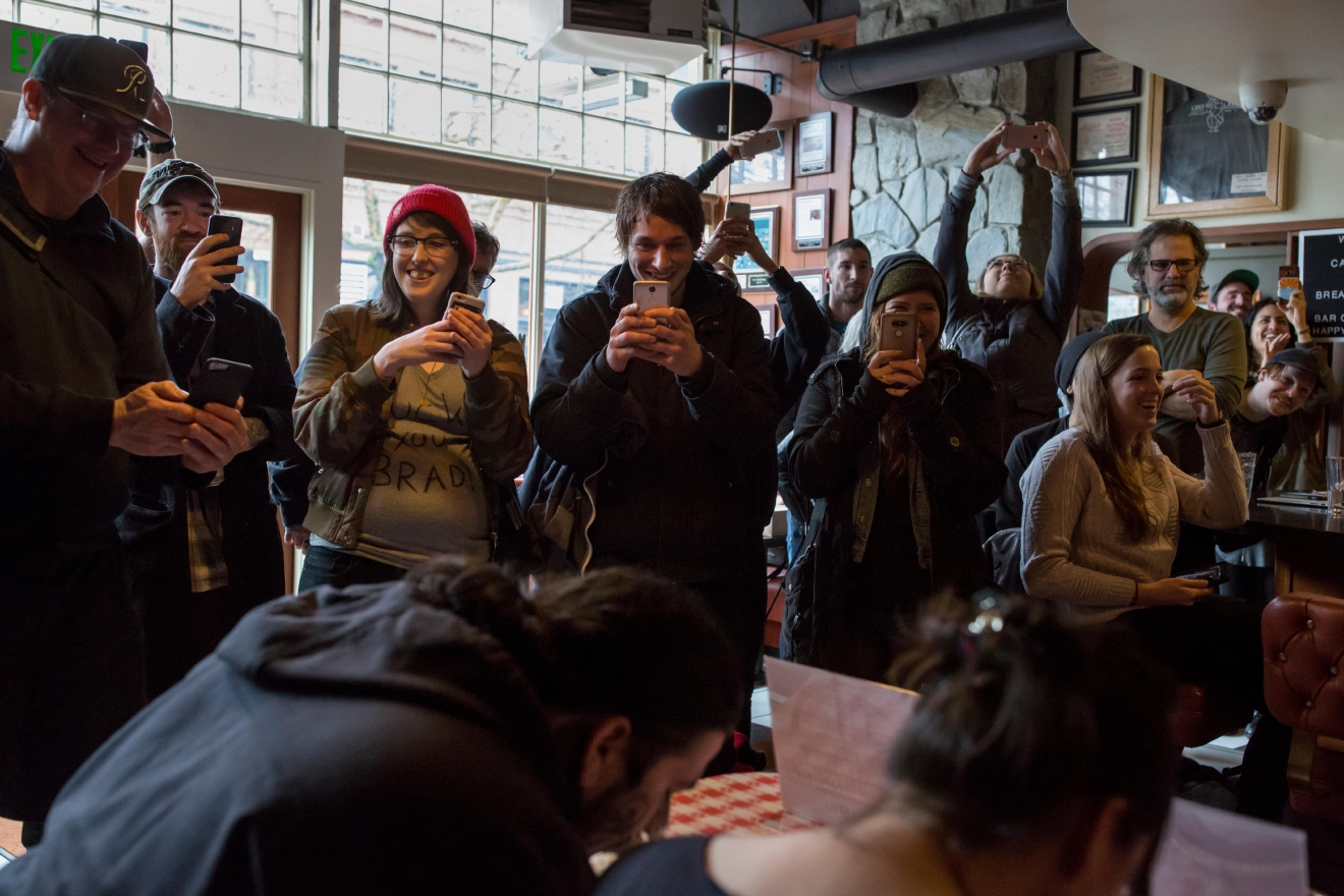 Spectators snap photos as participants race to eat a chocolate pie during the second annual Pi Day Pie Eating Contest at Lost Lake Cafe. The winner of the contest got to choose a charity of their choice to receive $500. (Sy Bean / Seattle Refined)
