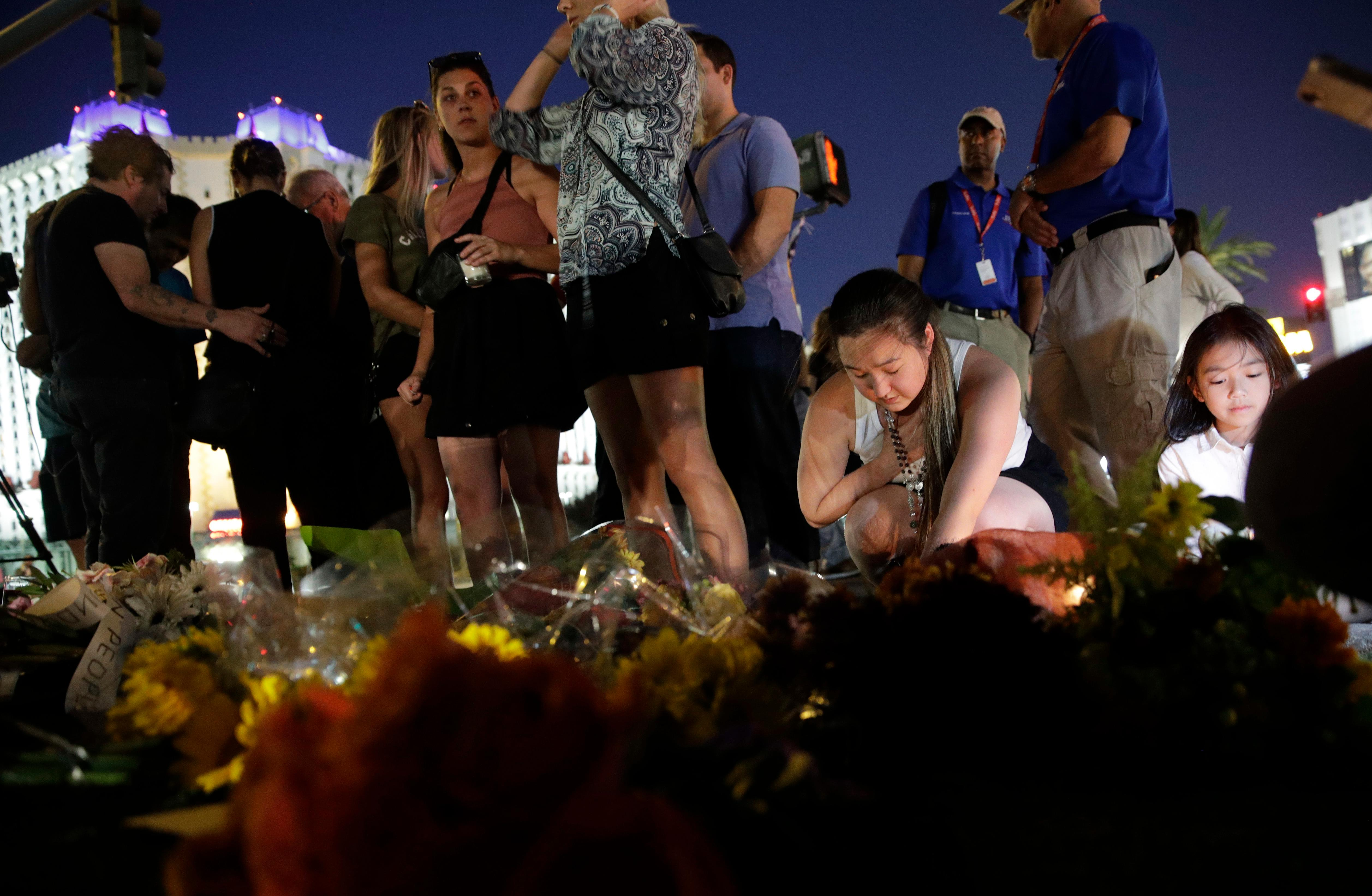 People pause at a memorial set up for victims of a mass shooting in Las Vegas, on Tuesday, Oct. 3, 2017. A gunman opened fire on an outdoor music concert on Sunday. It was the deadliest mass shooting in modern U.S. history, with dozens of people killed and hundreds injured, some by gunfire, some during the chaotic escape. (AP Photo/John Locher)