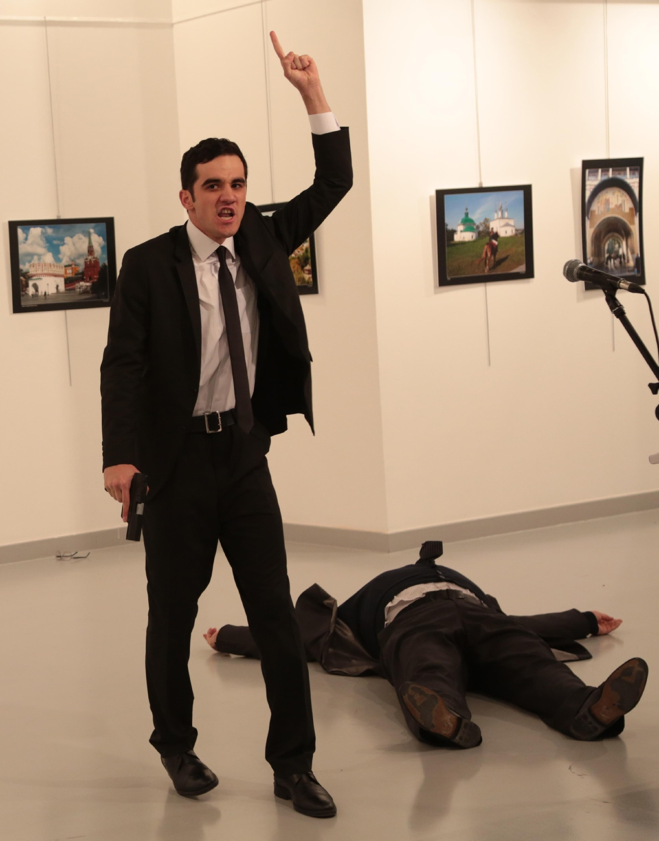 A gunman gestures near to Andrei Karlov, the Russian Ambassador to Turkey, on the ground, at a photo gallery in Ankara, Turkey, Monday, Dec. 19, 2016. An Associated Press photographer says a gunman has fired shots at the Russian ambassador to Turkey. The ambassador's condition wasn't immediately known. (AP Photo/Burhan Ozbilici)