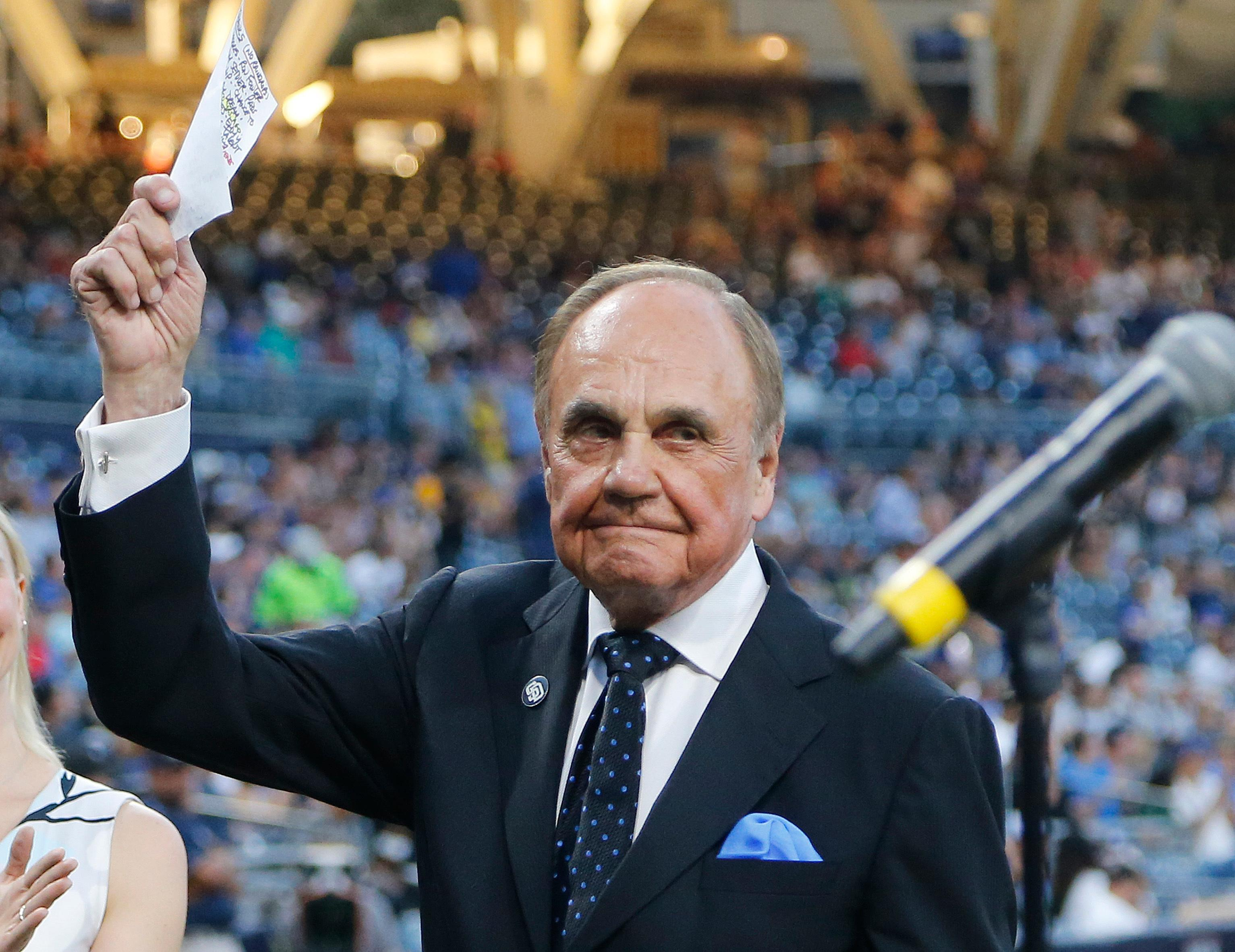 FILE - In this Sept. 29, 2016, file photo, San Diego Padres broadcaster Dick Enberg waves to crowd at a retirement ceremony prior to the Padres' final home baseball game of the season, against the Los Angeles Dodgers in San Diego. (AP Photo/Lenny Ignelzi, File)