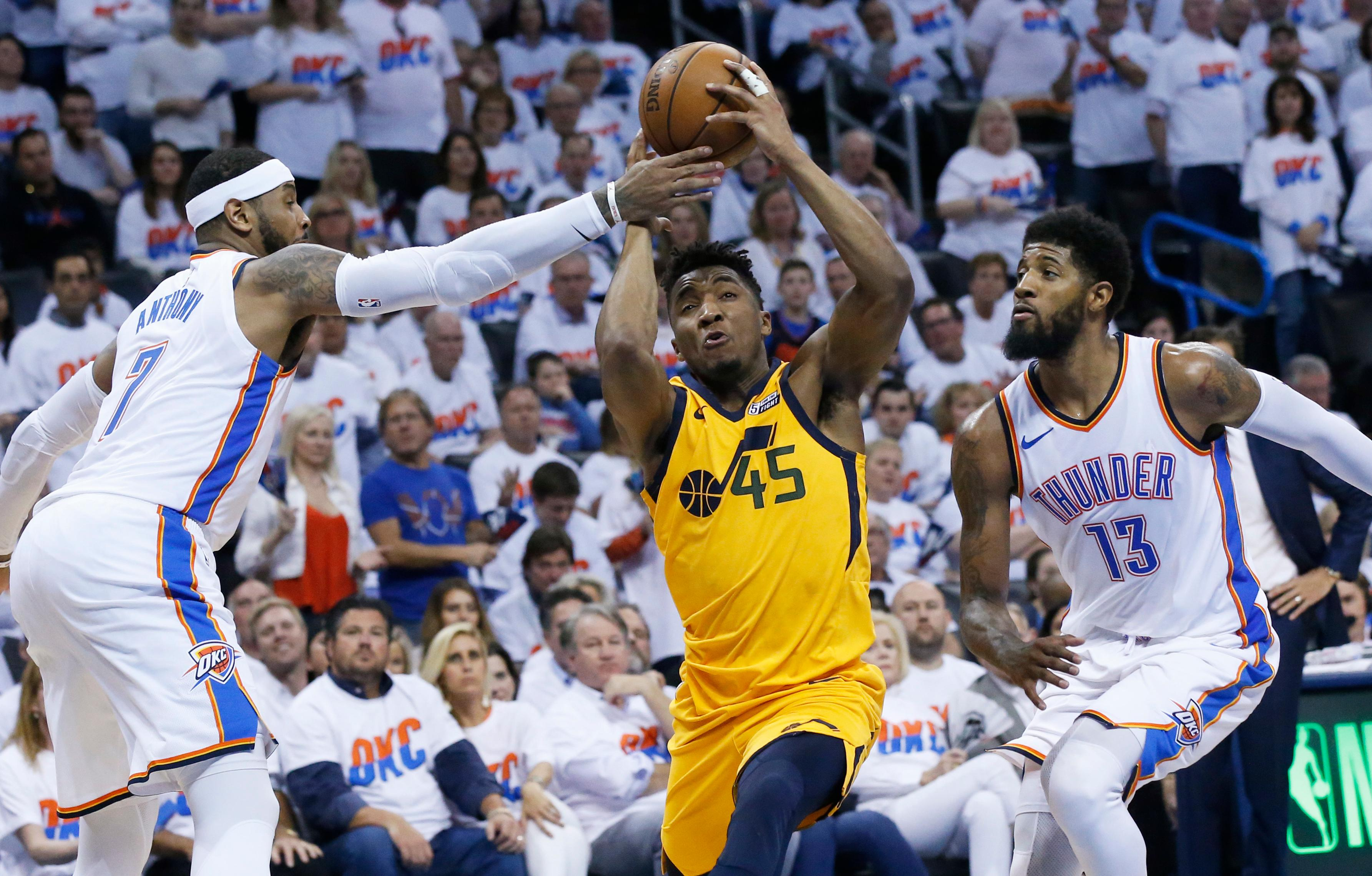 Oklahoma City Thunder forward Carmelo Anthony (7) reaches in to knock the ball away from Utah Jazz guard Donovan Mitchell (45) as Mitchell drives between Anthony and forward Paul George (13) in the second half of Game 2 of an NBA basketball first-round playoff series in Oklahoma City, Wednesday, April 18, 2018. (AP Photo/Sue Ogrocki)