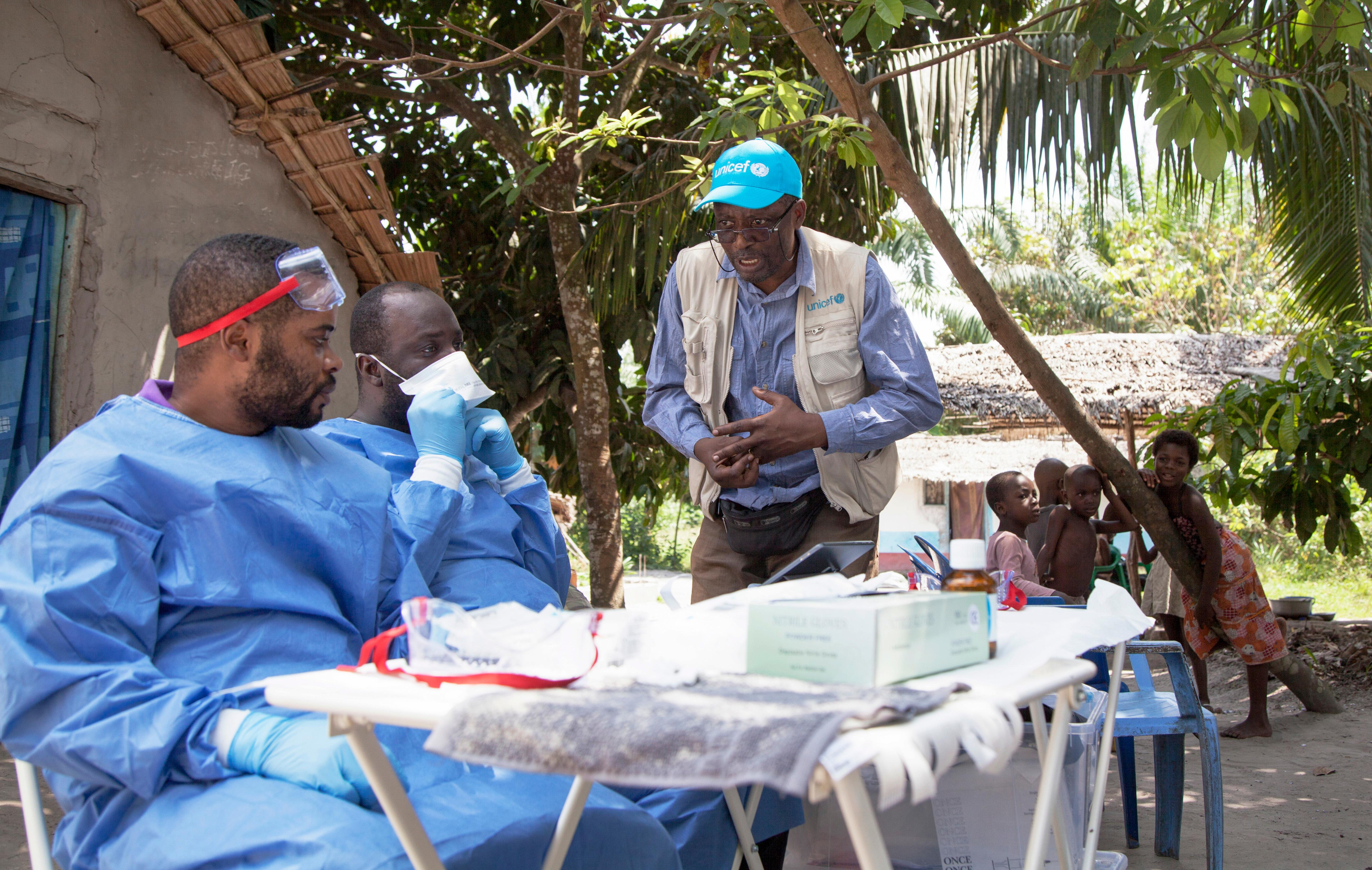 In this photo taken Friday, May 25, 2018, UNICEF staffer Jean Claude Nzengu, center, talks with members of an Ebola vaccination team as they prepare to administer the vaccine in an Ebola-affected community in the north-western city of Mbandaka, in Congo. An Ebola vaccination campaign is under way in Mbandaka, the city of 1.2 million on the Congo River where four Ebola cases have been confirmed. (Mark Naftalin/UNICEF via AP)