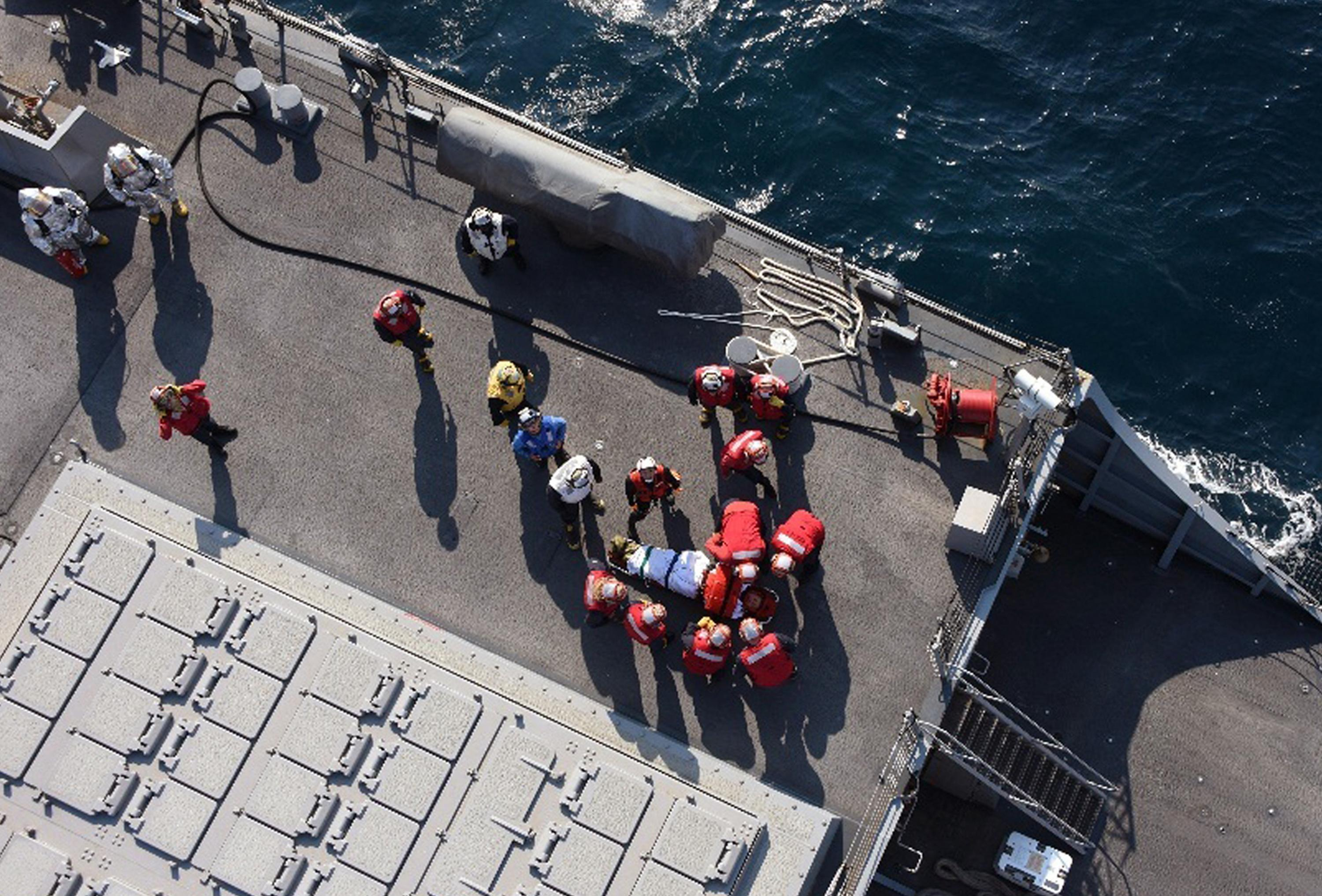 U.S. military personnel prepare to transfer an injured on board USS Fitzgerald, off Izu Peninsula,  Japan, after the Navy destroyer collided with a merchant ship, Saturday,  June 17, 2017.  The Japan coast guard said it received an emergency call from a Philippine-registered container ship ACX Crystal early Saturday that it had collided with the Fitzgerald southwest of Yokusuka, Japan. (Japan's Defense Ministry via AP)