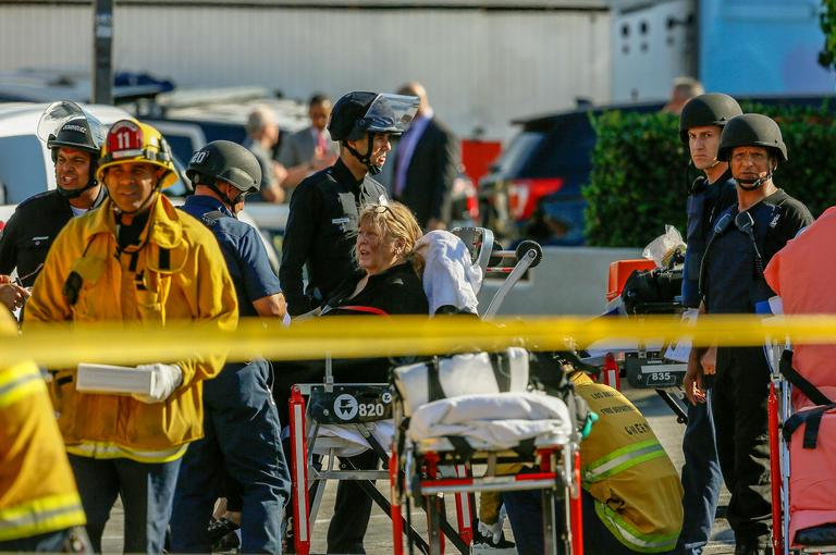 An unidentified woman is helped by paramedics at a triage area after a gunman held dozens of people hostage inside a Trader Joe's store in Los Angeles Saturday, July 21, 2018. Police believe a man involved in a standoff at the Los Angeles supermarket shot his grandmother and girlfriend and then fired at officers during a pursuit before he crashed into a utility pole outside the supermarket and ran inside the store. Hours after he took hostages in the store, the suspect surrendered. (AP Photo/Damian Dovarganes)