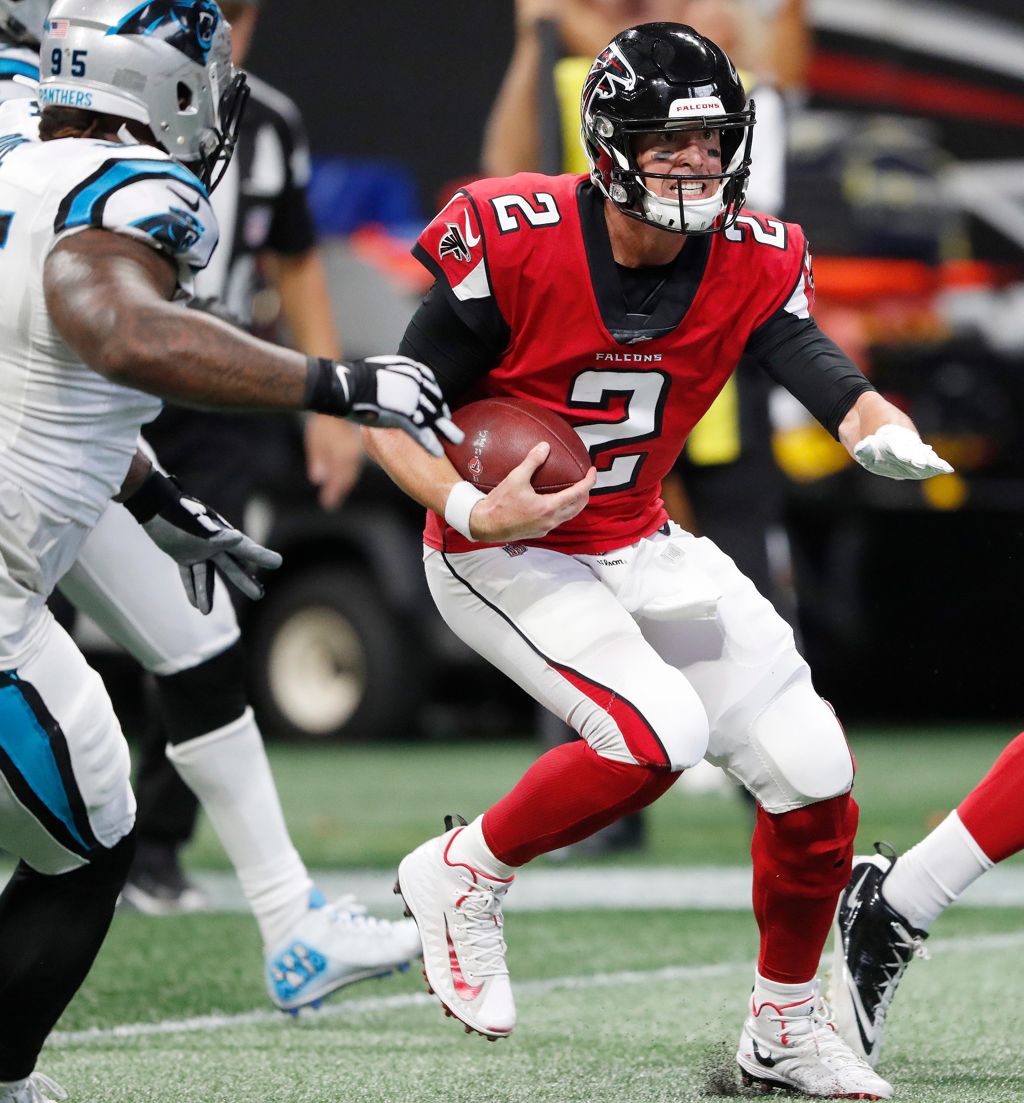 Atlanta Falcons quarterback Matt Ryan (2) runs through Carolina Panthers players during the second half of an NFL football game, Sunday, Sept. 16, 2018, in Atlanta. Ryan scored a touchdown on the play. (AP Photo/John Bazemore)
