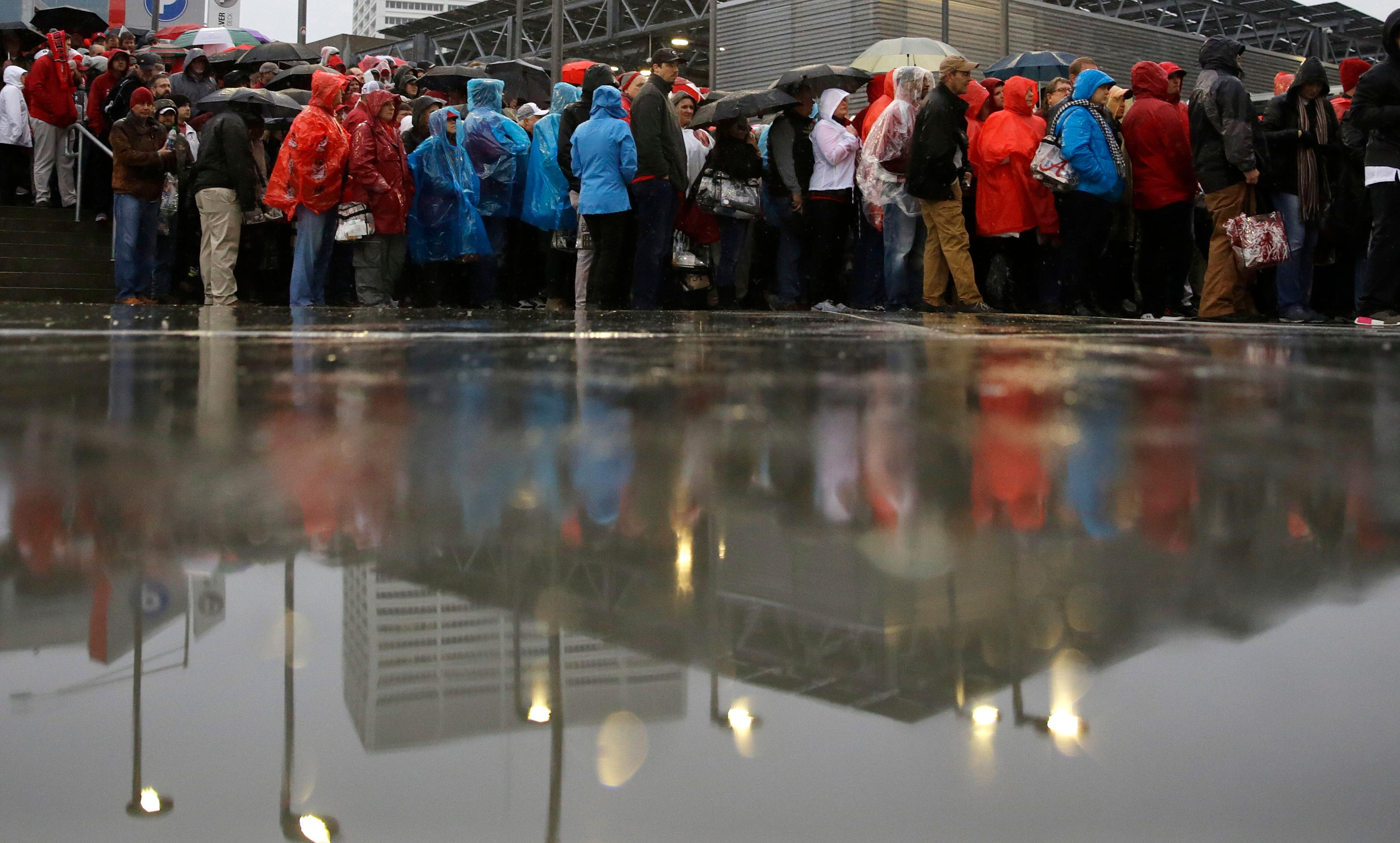 Fans wait outside Mercedes-Benz Stadium before the NCAA college football playoff championship game between Georgia and Alabama Monday, Jan. 8, 2018, in Atlanta. (AP Photo/David Goldman)