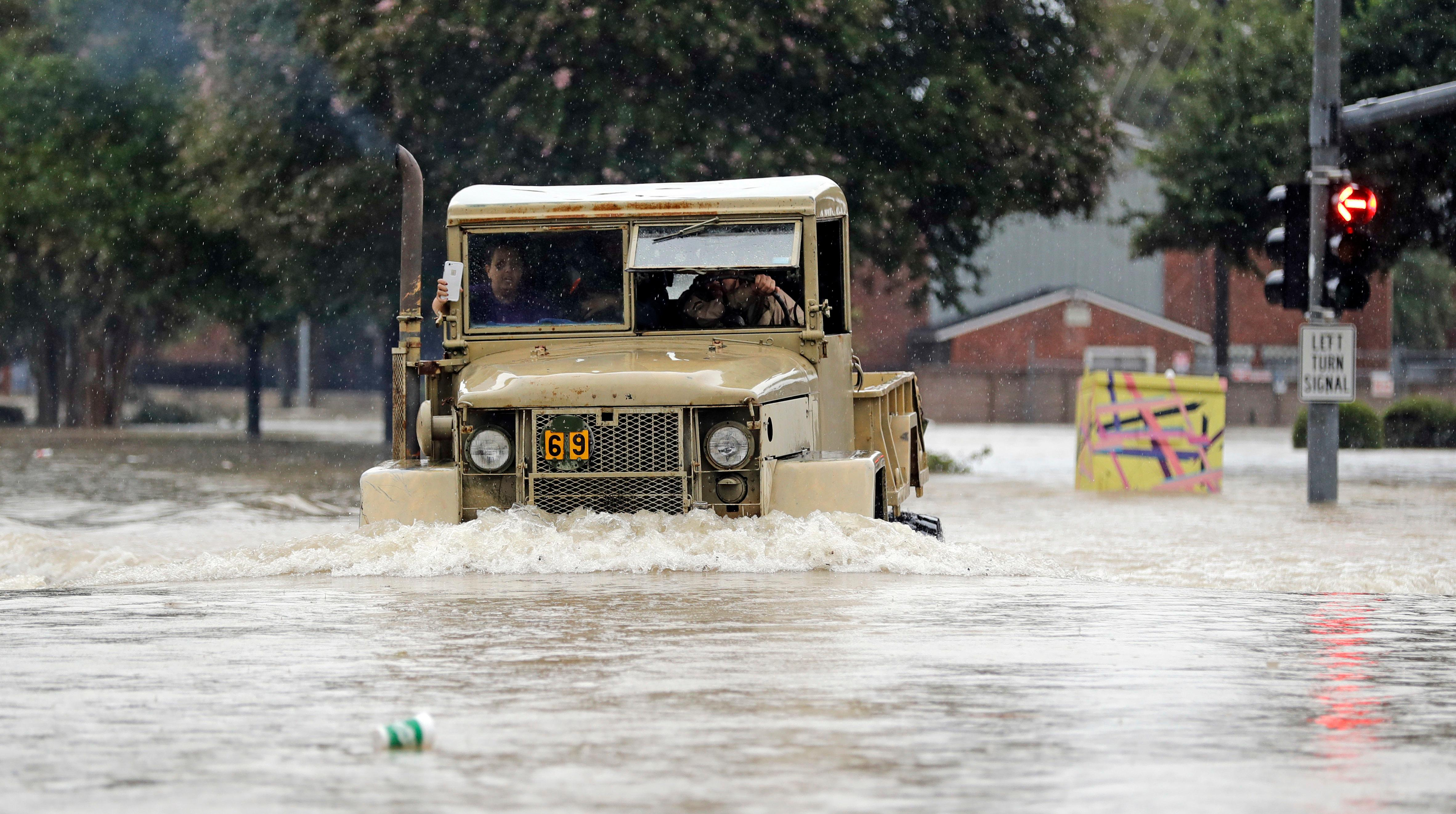 A truck pushes through floodwaters from Tropical Storm Harvey on Sunday, Aug. 27, 2017, in Houston, Texas. (AP Photo/David J. Phillip)