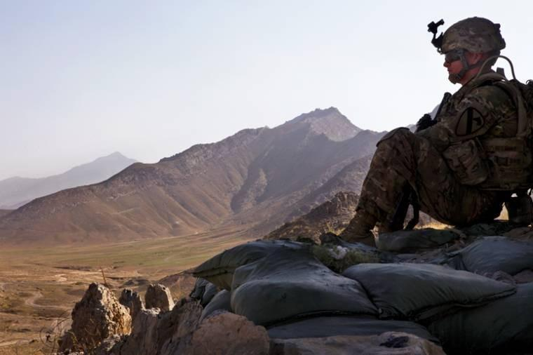U.S. Army Pfc. Jordan Adams provides security from a hilltop during a meeting with Afghan national police in Bagram. Adams is with the 1st Cavalry Division.  The national police have assumed responsibility for security throughout Afghanistan.