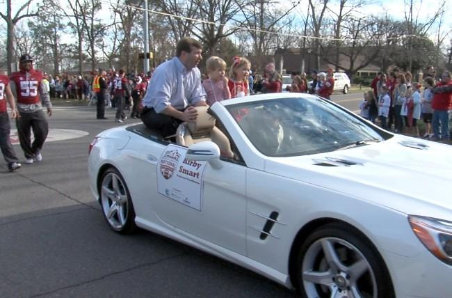 Alabama defensive coordinator Kirby Smart and his two children ride in a Mercedes Benz during the BCS Championship parade on Saturday, January 19, 2013.
