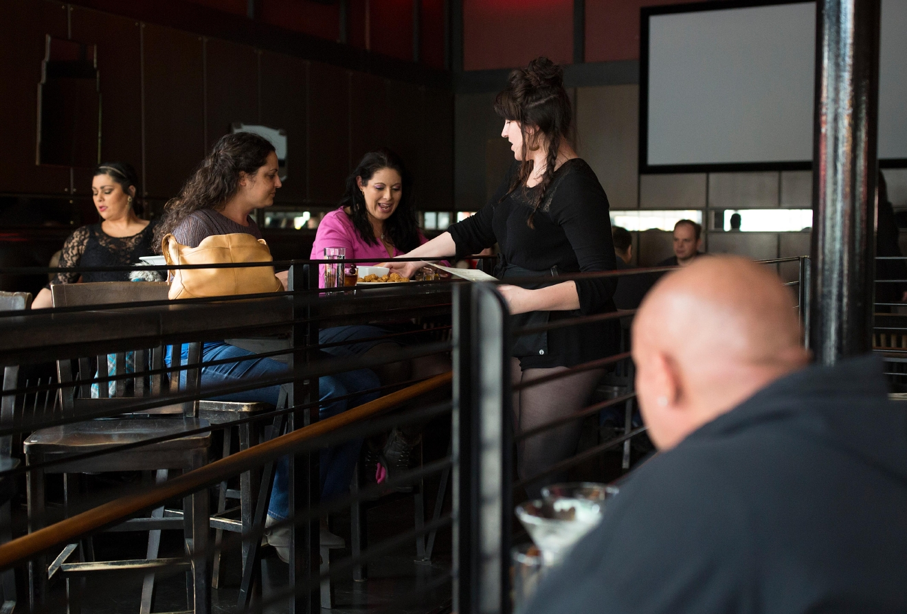 A waitress helps Anna Geisler, right, and Debi Scheenstra, as they get some of their last drinks at Tini Bigs Lounge on its final day of business. (Sy Bean / Seattle Refined)
