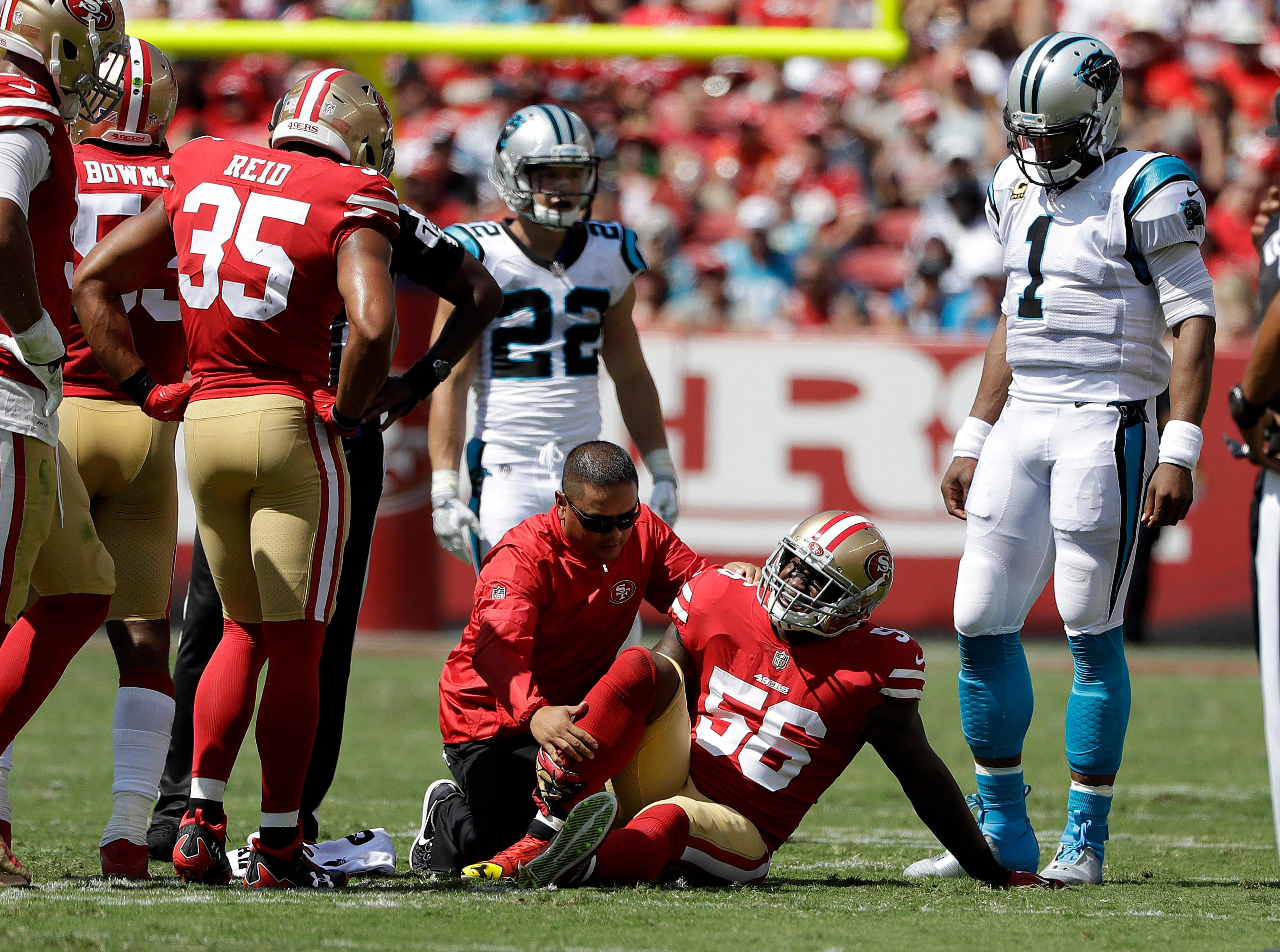 San Francisco 49ers linebacker Reuben Foster (56) is tended to by a trainer as teammates and Carolina Panthers quarterback Cam Newton (1) watch during the first half of an NFL football game in Santa Clara, Calif., Sunday, Sept. 10, 2017. (AP Photo/Marcio Jose Sanchez)