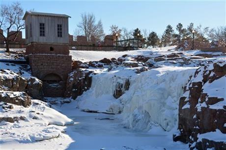 The waterfalls at Falls Park sit frozen with just a trickle of water flowing underneath, Sunday, Jan. 5, 2014, in Sioux Falls, S.D.