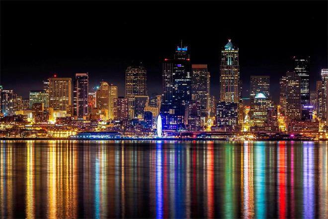 Seattle waterfront all lit up from Alki Beach. Photo Credit: Bob Noble Photography