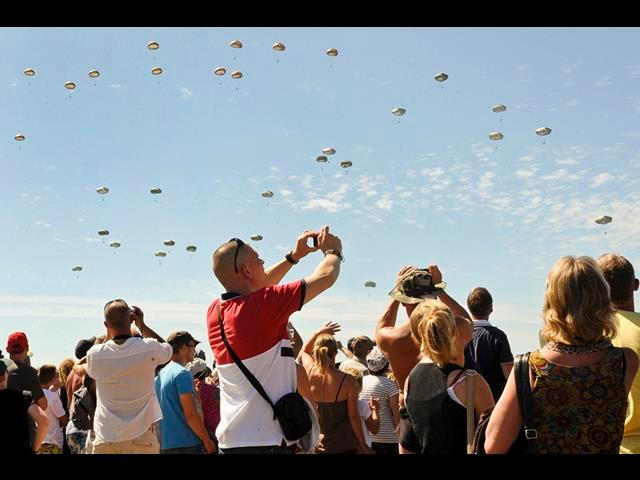 Thousands of people photograph U.S. and international paratroopers as they land in the Normandy region of France, June 8, 2014, to commemorate the 70th anniversary of D-Day.