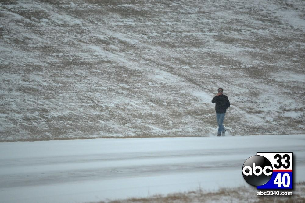 A stranded motorist walks along Interstate 459 West near Hoover, Ala. during a winter storm, Tuesday, January 28, 2014.