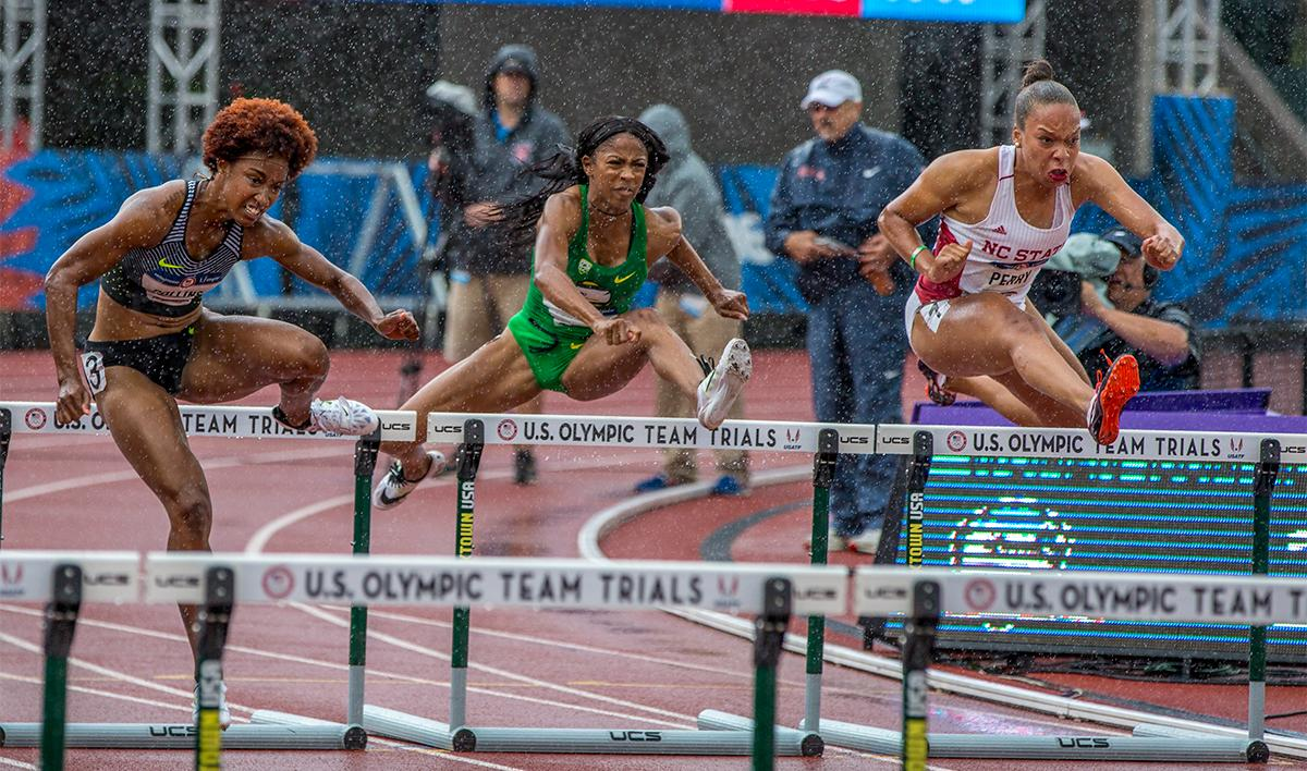 Rain thunders down on the competitors in the 100 meter hurdles. In the center, Oregon's Alaysha Johnson strides over the hurdles. Johnson finished fifth in her heat with a time of 13.03. Photo by August Frank, Oregon News Lab