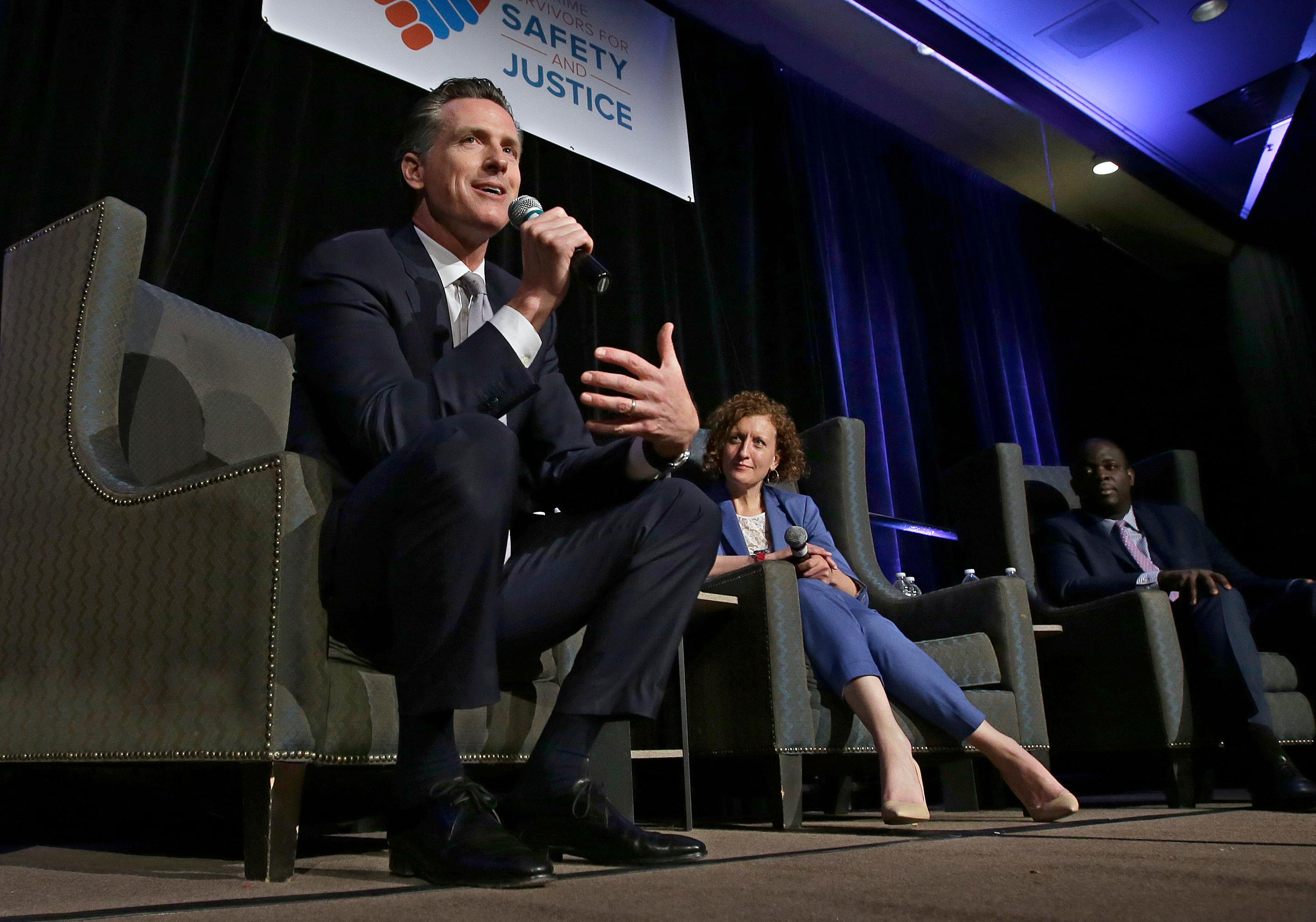 Lt. Gov. Gavin Newsom, a candidate for California governor, speaks at a gubernatorial candidates forum, Tuesday, April 4, 2017, in Sacramento, Calif. Newsom along with fellow Democratic gubernatorial candidates, state Treasurer John Chiang and former Los Angeles Mayor Antonio Villaraigosa addressed attendees at a conference held by Crime Survivors For Safety and Justice. In the center is Lenore Anderson, founder and executive director of Crime Survivors For Safety and Justice and at right is Alex Johnson, the managing director.  (AP Photo/Rich Pedroncelli)
