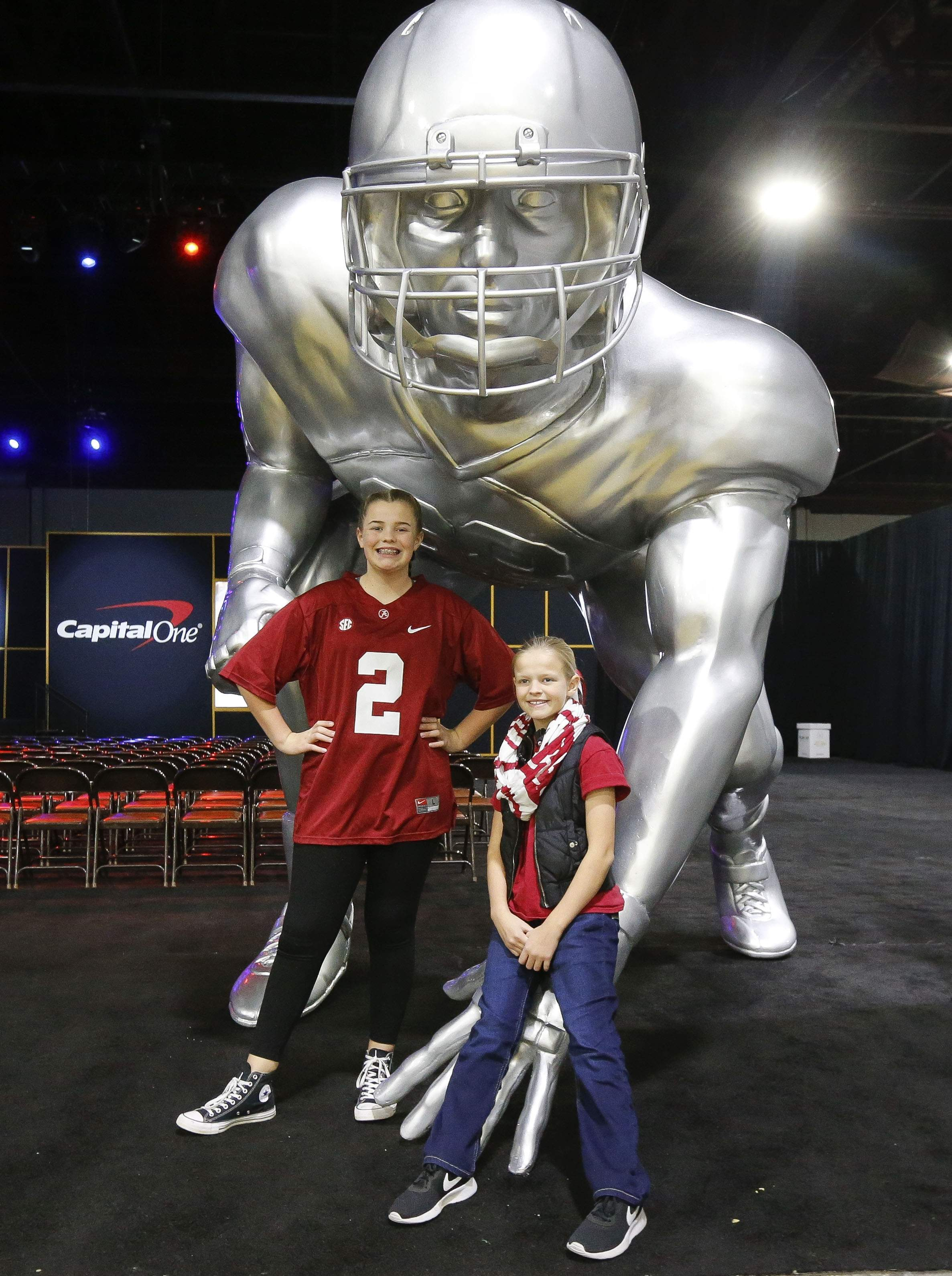 Alabama fans Mattie and Lily Brookshire pose for a photo with a giant football statue as Alabama and Georgia fans enjoy activities at the Georgia World Congress Center Sunday, Jan. 7, 2018. [Gary Cosby Jr./The Tuscaloosa News]