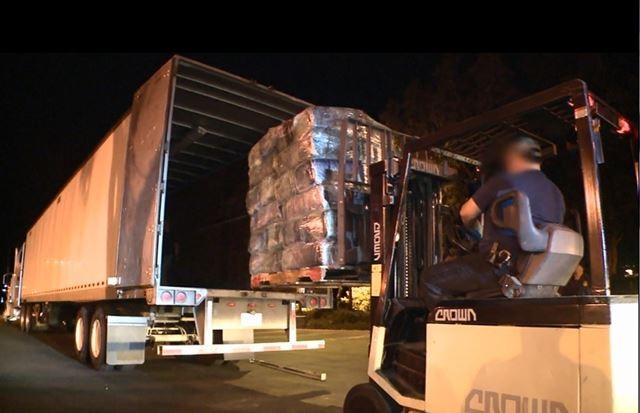 The marijuana and cocaine are loaded into a waiting semi-truck.