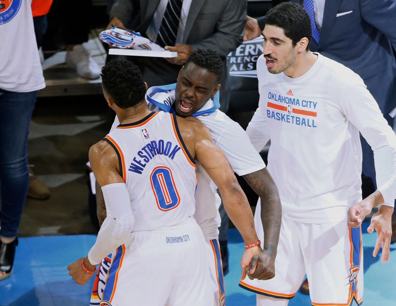 Oklahoma City Thunder guard Russell Westbrook (0) celebrates with teammates Andrew Morrow, center, and Enes Kanter, right, following a basket against the Golden State Warriors in Game 4 of the NBA basketball Western Conference finals in Oklahoma City, Tuesday, May 24,, 2016. The Thunder won 118-94. (AP Photo/Sue Ogrocki)