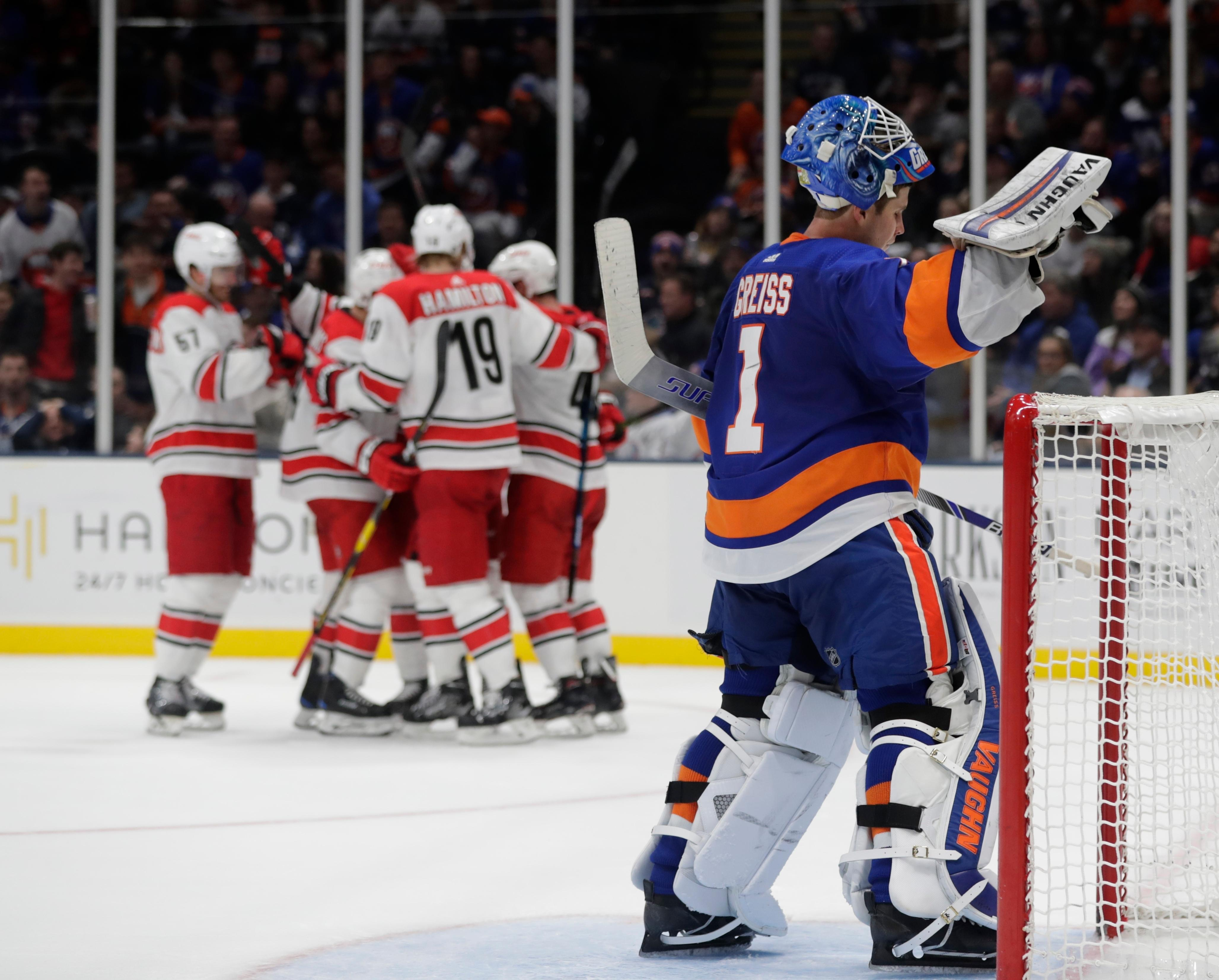 New York Islanders goaltender Thomas Greiss (1) reacts as the Carolina Hurricanes celebrate a goal by Justin Williams (14) during the third period of an NHL hockey game Tuesday, Jan. 8, 2019, in New York. The Hurricanes won 4-3. (AP Photo/Frank Franklin II)