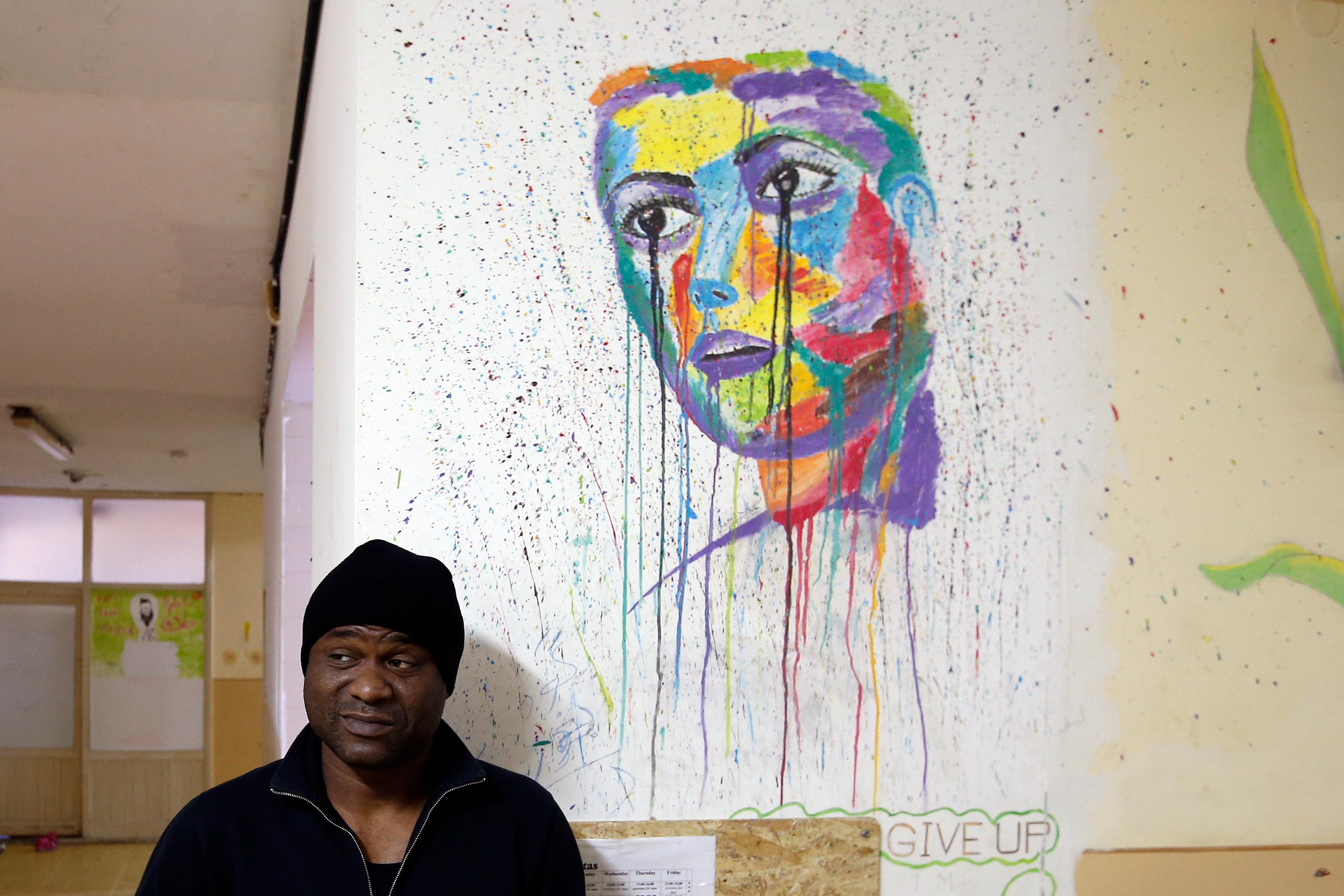 A Cuban migrant Michael Amor stand by a mural in the center for refugees in Sot, about 100 km west from Belgrade, Serbia, Thursday, Feb. 1, 2018. Far away from sandy beaches and a balmy Caribbean breeze, a Cuban family huddles together in a cramped room of a Serbian refugee center, trying to figure out what to do next. They are part of an unlikely influx of Cuban migrants to the Balkans that began in 2015 before neighboring European Union countries sealed off their borders. Most Cuban migrants in Serbia say they had to make the trip after the U.S. revoked Cubans' special migration status last year.(AP Photo/Darko Vojinovic)