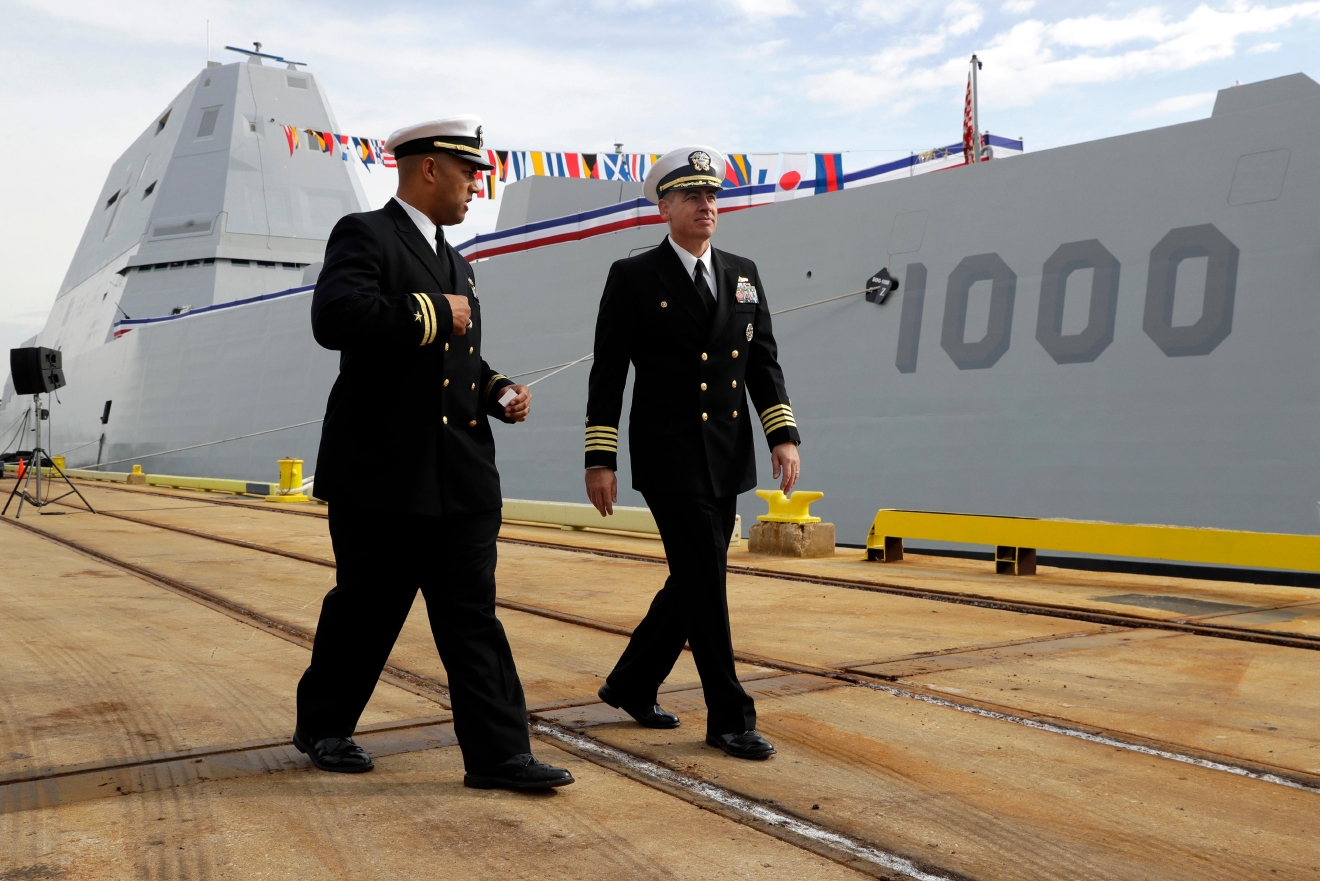 In this Oct. 13, 2016 photo, Lt. Rick Moore, left, and Capt. James Kirk, commanding officer of the future USS Zumwalt, walk past the ship to a news conference in Baltimore. Designed and built with an angular shape to minimize its radar signature, it's the most expensive destroyer ever built for the Navy. (AP Photo/Patrick Semansky)