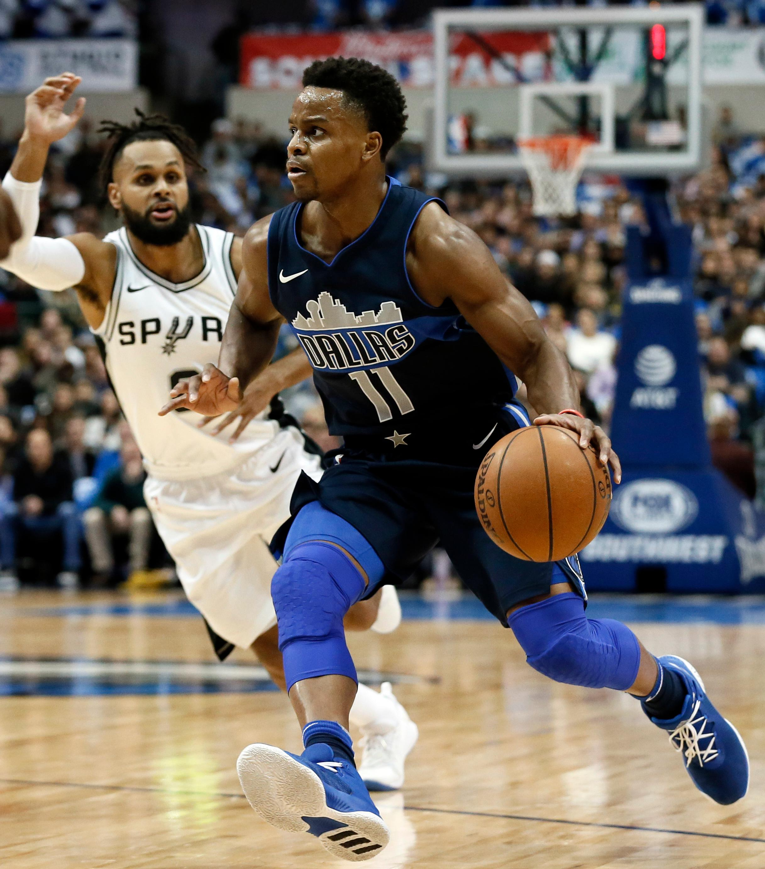 Dallas Mavericks guard Yogi Ferrell (11) gets past San Antonio Spurs' Patty Mills (8) on a drive to the basket in the first half of an NBA basketball game, Tuesday, Dec. 12, 2017, in Dallas. (AP Photo/Tony Gutierrez)