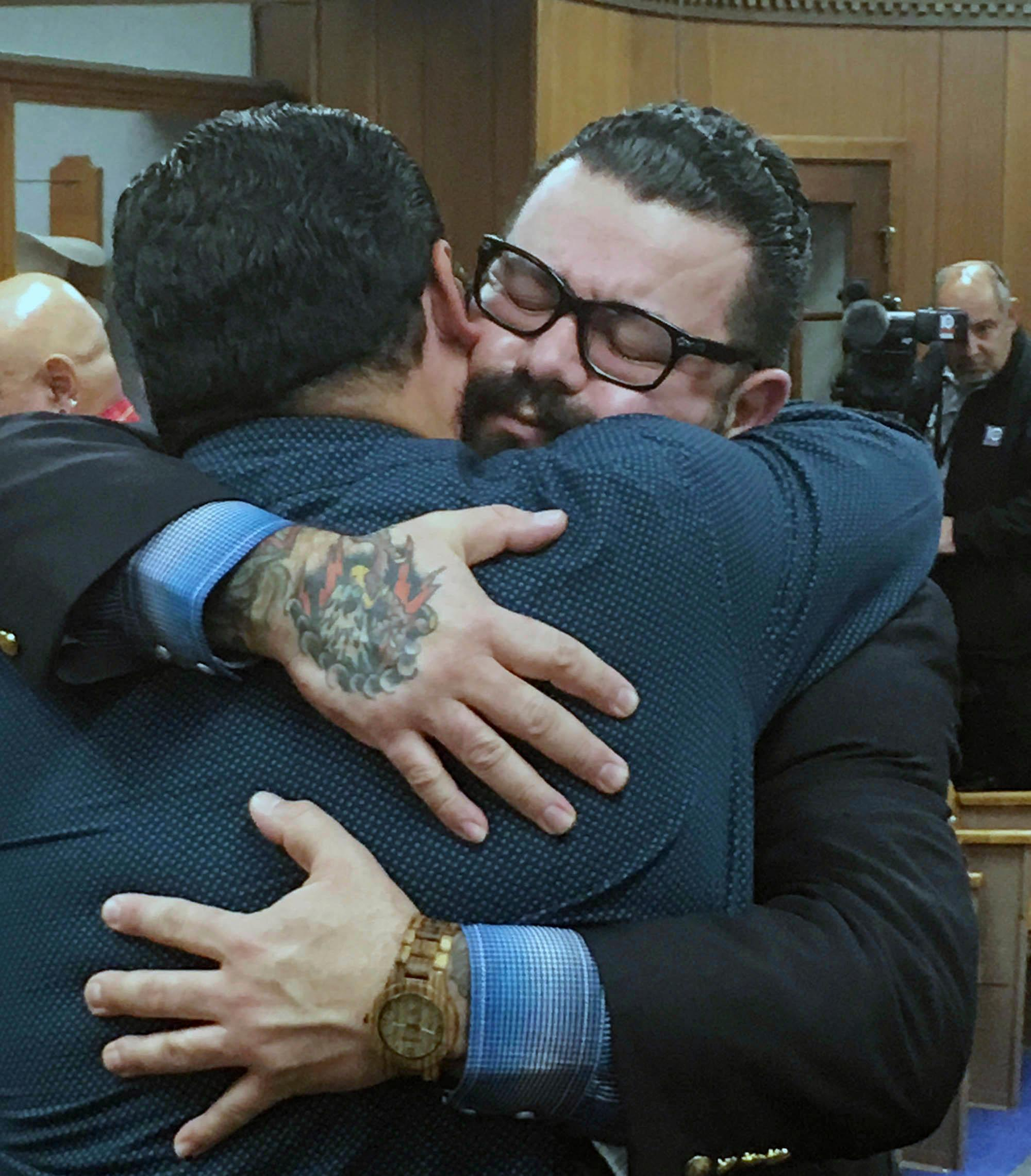 "Christopher ""Jake"" Carrizal, right, gets a hug following a mistrial, Friday, Nov. 10, 2017, in Waco, Texas. The Dallas chapter president of the Bandidos motorcycle club is the first to stand trial involving the 2015 shootout where nine people were fatally shot and 18 people were injured outside of Twin Peaks restaurant. (Tommy Witherspoon/Waco Tribune-Herald via AP)"