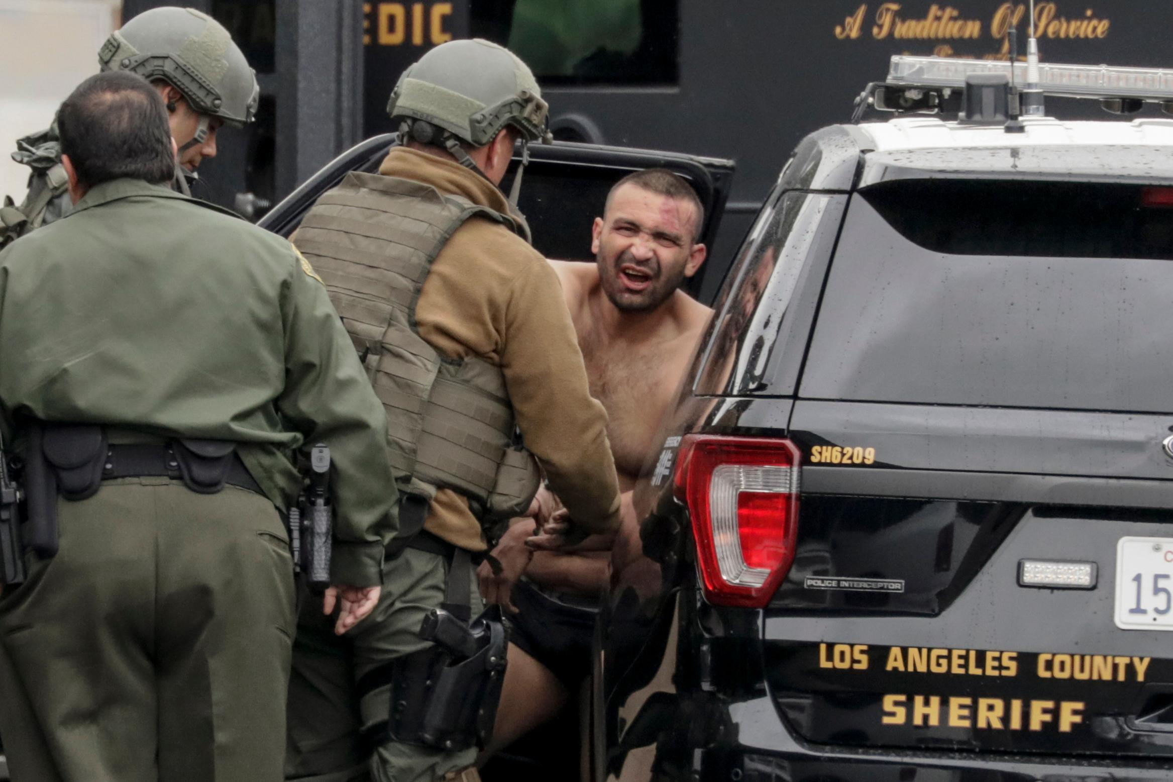 Los Angeles County Sheriff deputies escort a handcuffed man suspected of fatally shooting a Pomona police officer to a waiting car Saturday, March 10, 2018, in Pomona, Calif. (Irfan Khan/Los Angeles Times via AP)