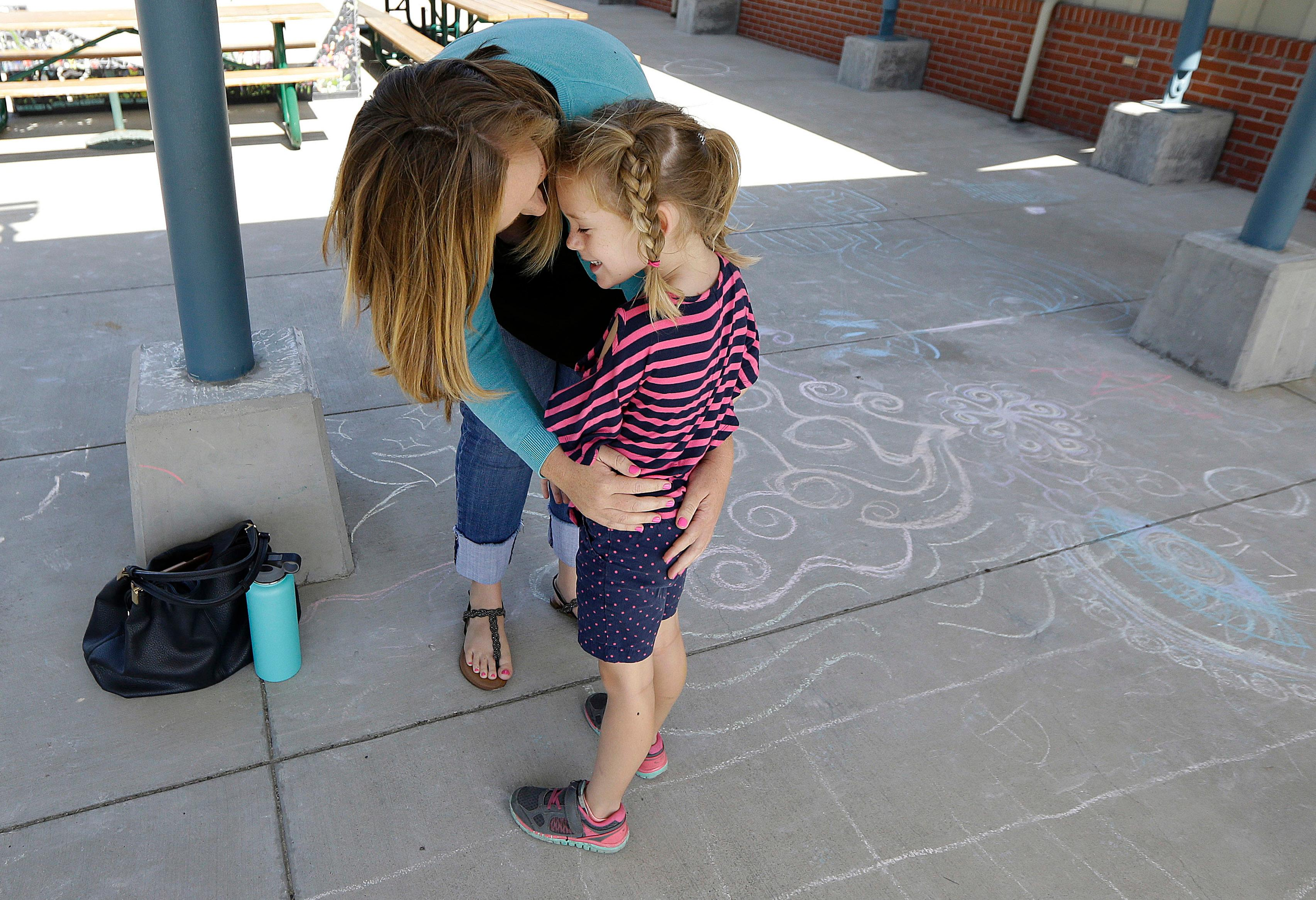 "In this Tuesday, July 11, 2017 photo, Molly Maxwell hugs her child Gracie at the Bay Area Rainbow Day Camp in El Cerrito, Calif. The camp caters to transgender and ""gender fluid"" children, aged 4-12, making it one of the only camps of its kind in the world open to preschoolers, experts say. (AP Photo/Jeff Chiu)"