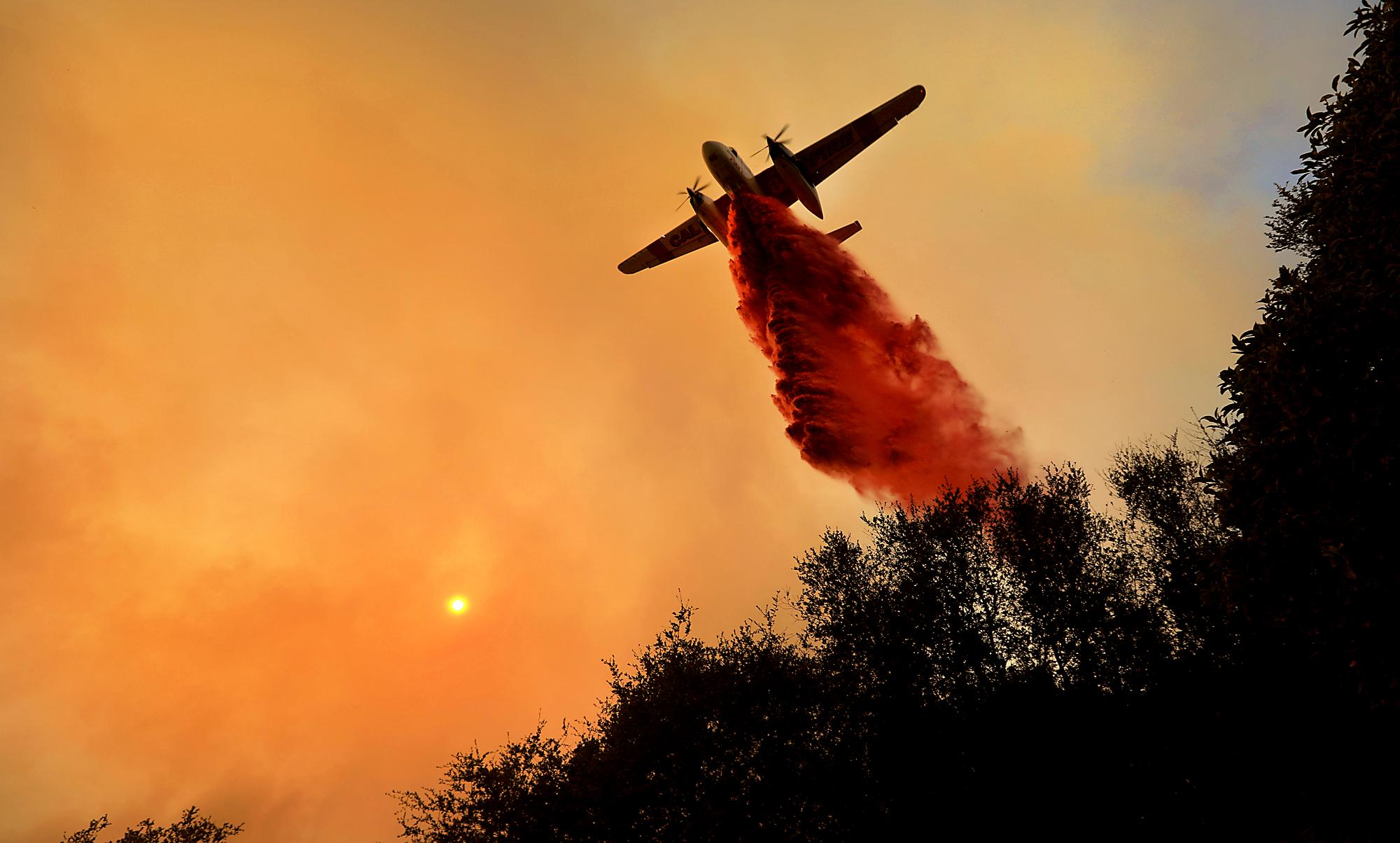 A Cal Fire air taker makes a drop on a wildfire as the pilot protects structures on the Hawkeye Ranch above Geyserville, Thursday Oct. 12, 2017. Thousands of firefighters are battling the blazes and additional manpower and equipment was pouring in from across the country and as far as Australia and Canada. (Kent Porter/The Press Democrat via AP)